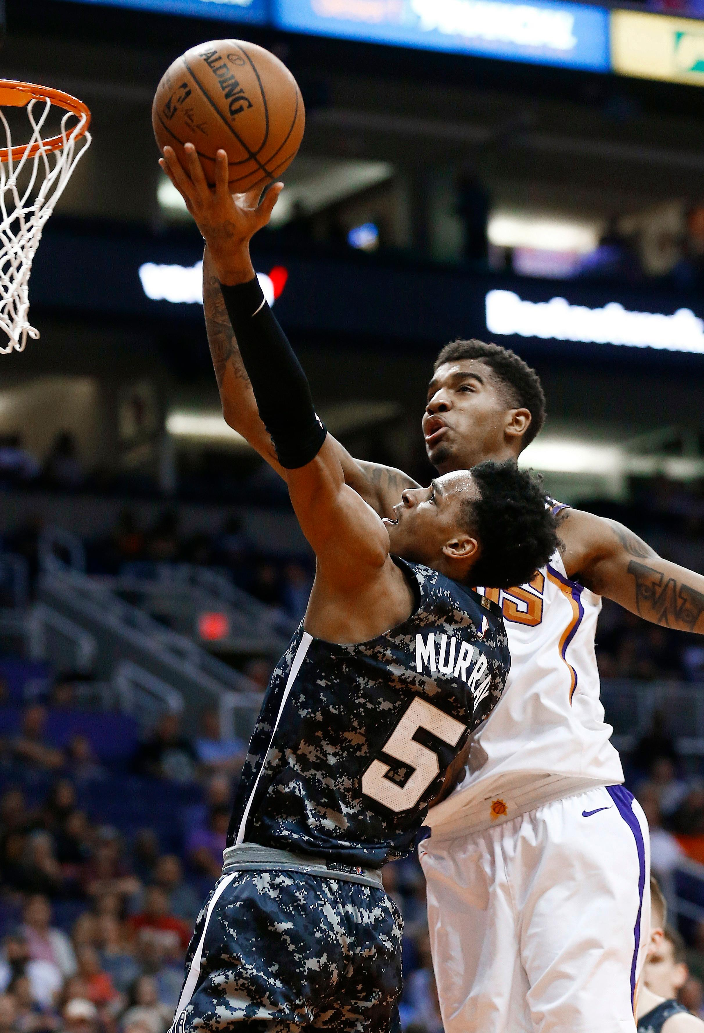 San Antonio Spurs guard Dejounte Murray (5) drives past Phoenix Suns forward Marquese Chriss, right, to score during the first half of an NBA basketball game Wednesday, Feb. 7, 2018, in Phoenix. (AP Photo/Ross D. Franklin)