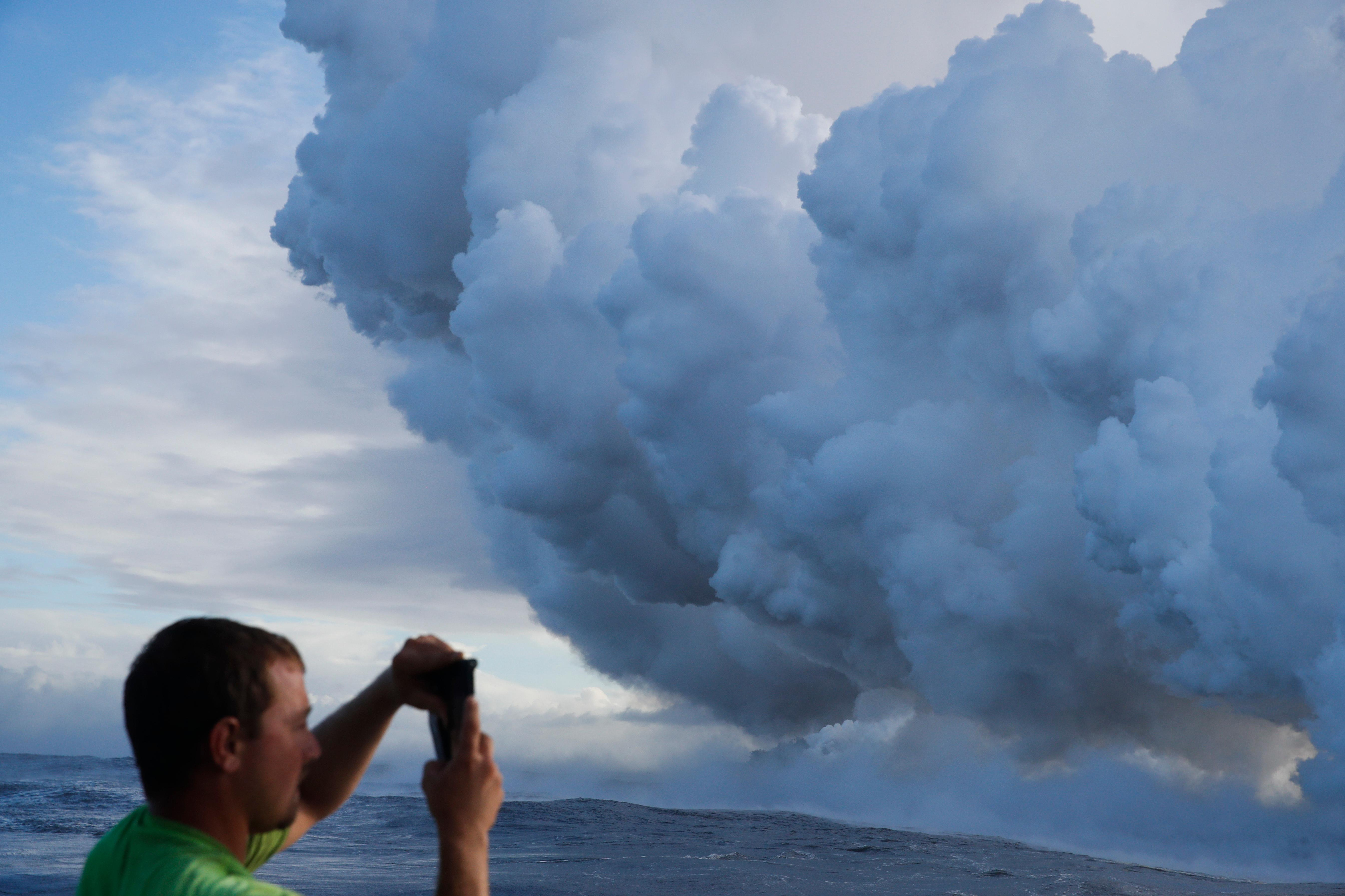 Joe Kekedi takes pictures of a plume of steam as lava enters the ocean near Pahoa, Hawaii, Sunday, May 20, 2018. Kilauea volcano that is oozing, spewing and exploding on Hawaii's Big Island has gotten more hazardous in recent days, with rivers of molten rock pouring into the ocean Sunday and flying lava causing the first major injury. (AP Photo/Jae C. Hong)