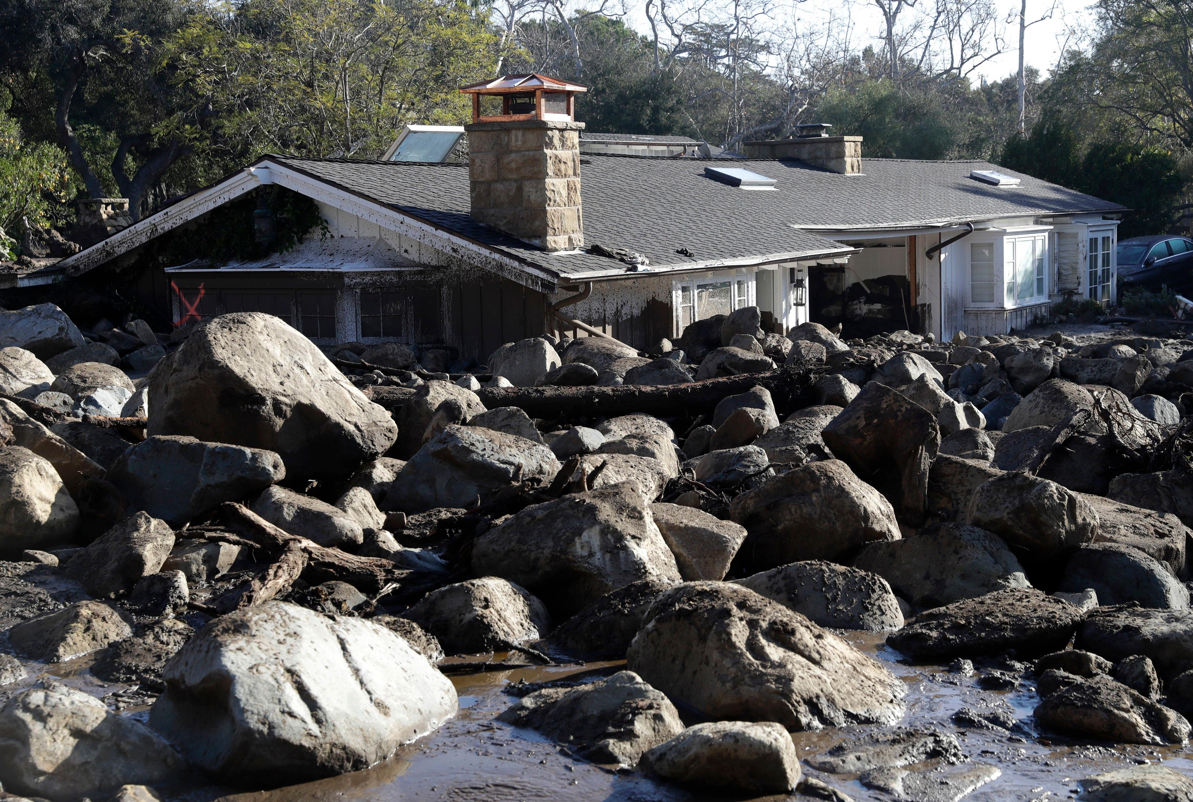 Large rocks and mud are shown in front of a house in Montecito, Calif., Thursday, Jan. 11, 2018. Hundreds of rescue workers slogged through knee-deep ooze and used long poles to probe for bodies Thursday as the search dragged on for victims of the mudslides that slammed this wealthy coastal town. (AP Photo/Marcio Jose Sanchez)