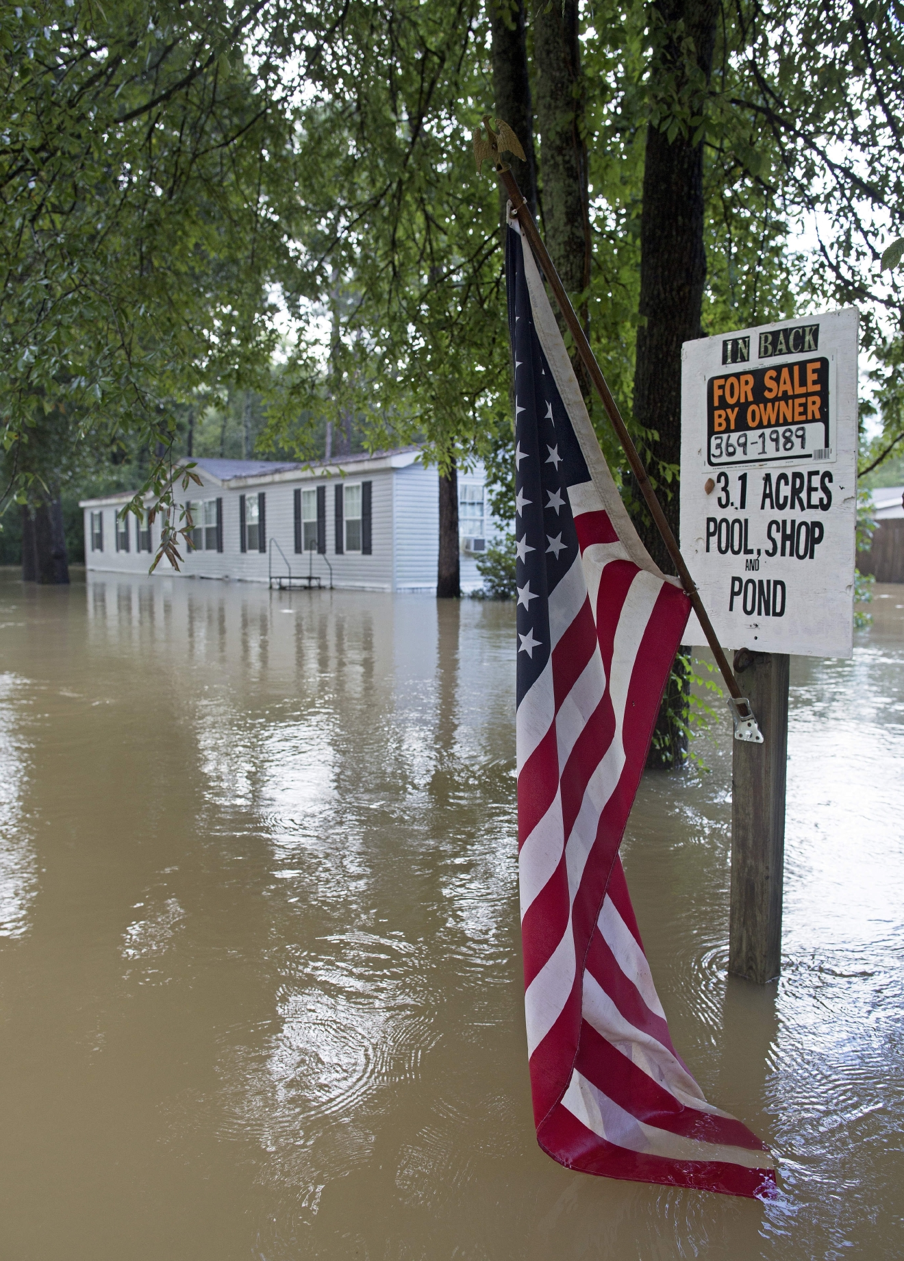 An American flag hangs in the water next to a for sale sign in flood waters in Walker, La., Monday, Aug. 15, 2016. Flood waters continued to cause problems throughout the area. (AP Photo/Max Becherer)