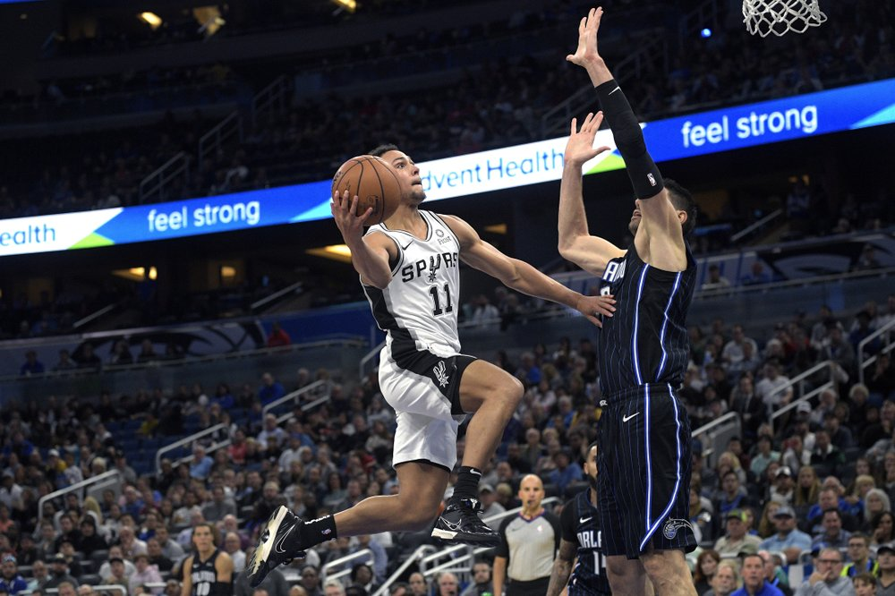 San Antonio Spurs guard Bryn Forbes (11) goes up to shoot in front of Orlando Magic center Nikola Vucevic, right, during the first half of an NBA basketball game Friday, Nov. 15, 2019, in Orlando, Fla. (AP Photo/Phelan M. Ebenhack)