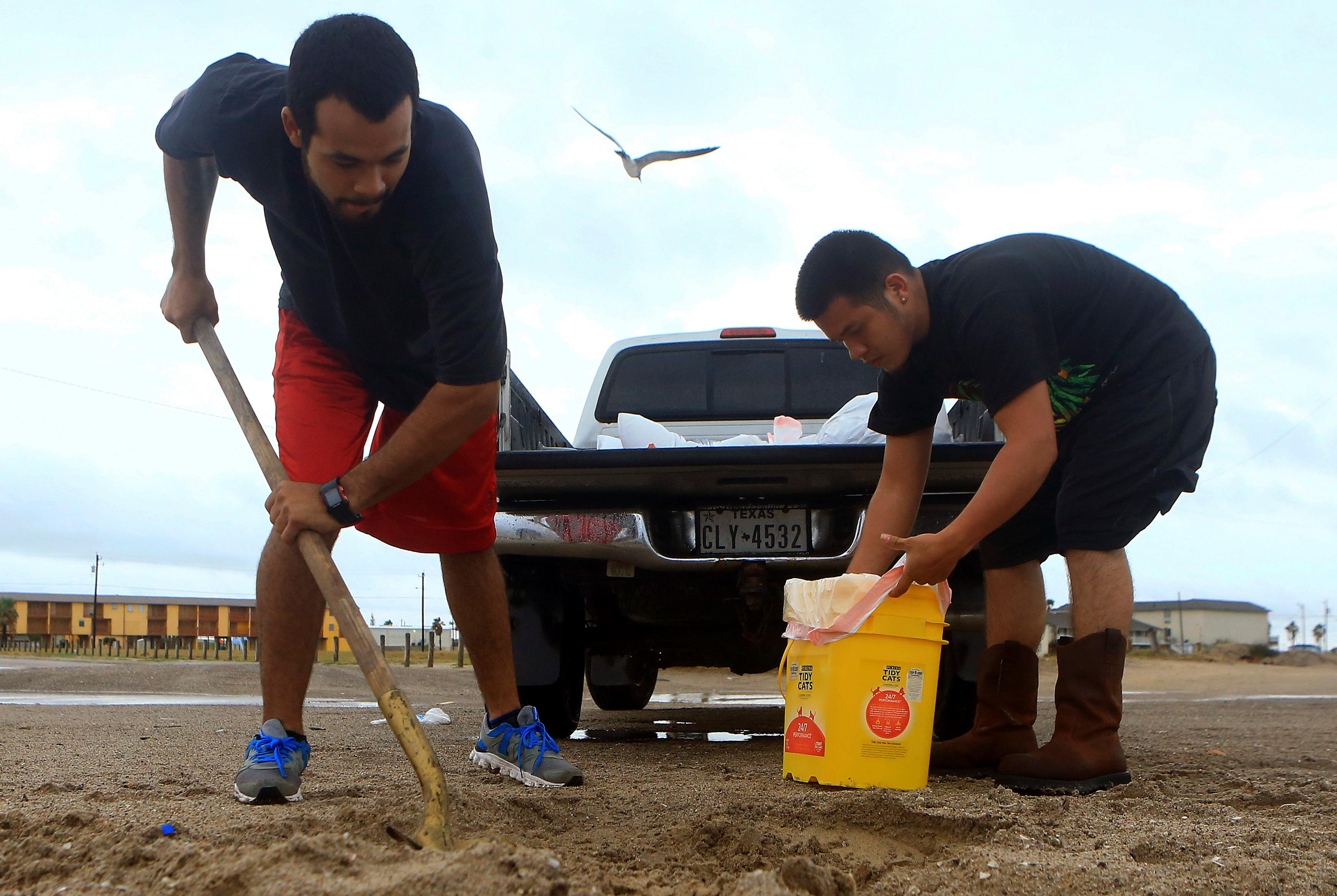 Oscar Aldana, left, and Abraham Blanco prepare sandbags to take home as Hurricane Harvey approaches the Coastal Bend area on Friday, Aug. 25, 2017, in Corpus Christi, Texas. The National Hurricane Center warns that conditions are deteriorating as Hurricane Harvey strengthens and slowly moves toward the Texas coast. (Gabe Hernandez/Corpus Christi Caller-Times via AP)