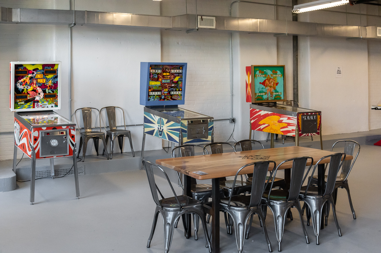 The inside of the brewery has a raw, industrial aesthetic. The building was originally built in 1925 as a parking garage with a massive elevator that would lift and lower cars to their desired floor. Today, the former garage houses all of Rebel Mettle's production as well as two stories of seating and free-to-play retro games, like pinball and skeeball. A horseshoe bar sits in the middle of the first floor, and a mezzanine with perimeter seating and a satellite bar occupies the second floor. / Image: Phil Armstrong, Cincinnati Refined // Published: 10.21.20