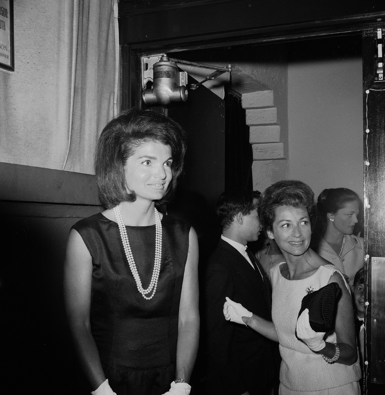 Former first lady Jacqueline Kennedy enters the Theater de Lys in New York's Greenwich Village for a musical performance of Leonard Bernstein songs, July 28, 1965. Others are unidentified.  (AP Photo/John Lent)