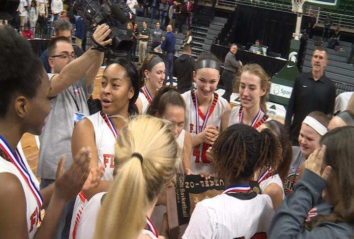 The Flushing girls basketball team celebrates after winning the Class A State Championship.