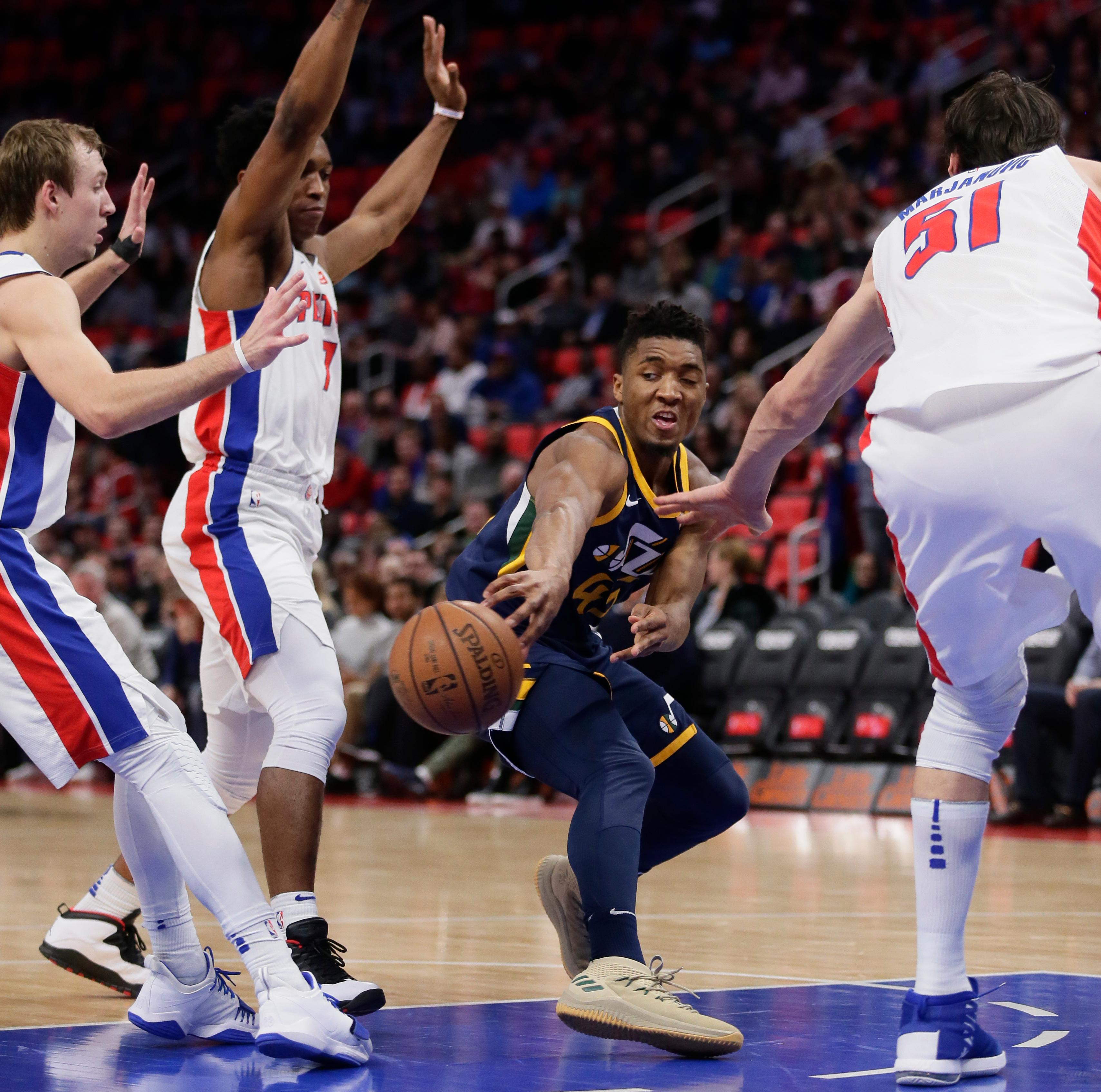 Utah Jazz guard Donovan Mitchell (45) passes the ball against Detroit Pistons guard Luke Kennard, left, forward Stanley Johnson and center Boban Marjanovic (51) during the first half of an NBA basketball game Wednesday, Jan. 24, 2018, in Detroit. (AP Photo/Duane Burleson)