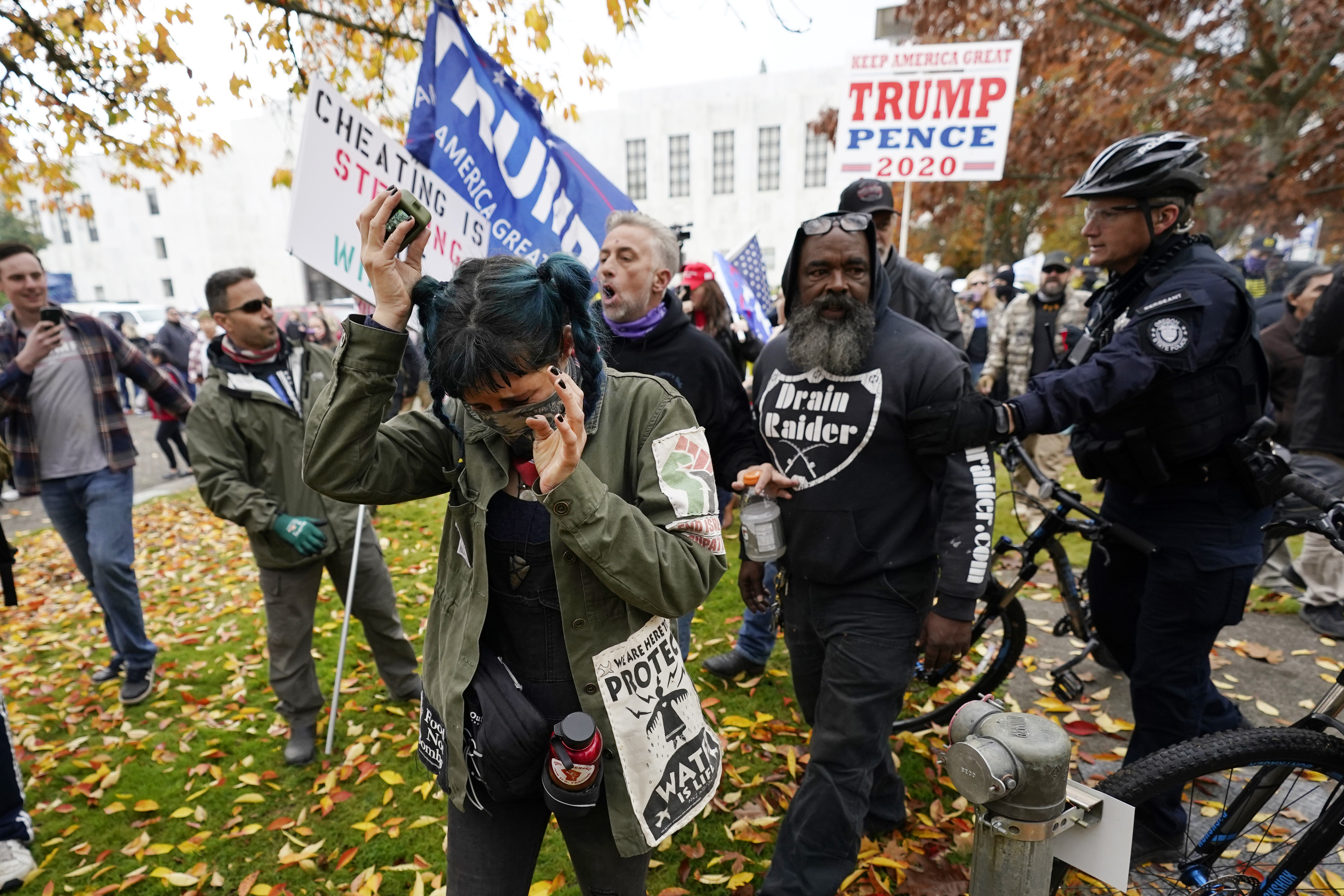 Supporters of President Trump follow a counter-protester as a police officer intervenes in front of the Oregon State Capitol building Saturday, Nov 7, 2020, in Salem, Ore., after Democrat Joe Biden defeated Trump to become 46th president of the United States. (AP Photo/Marcio Jose Sanchez)