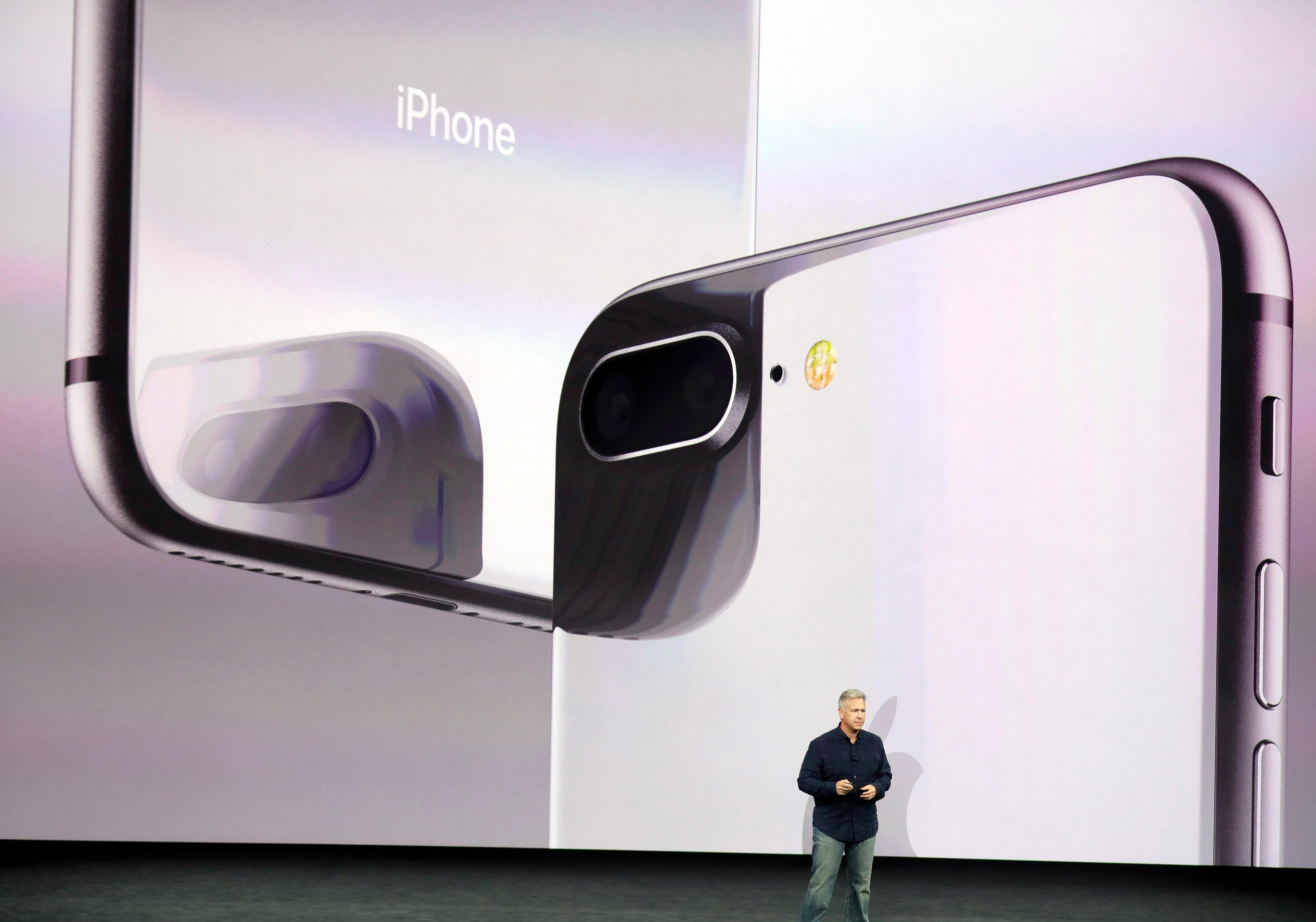 Phil Schiller, Apple's senior vice president of worldwide marketing, shows the new iPhone 8 at the Steve Jobs Theater on the new Apple campus on Tuesday, Sept. 12, 2017, in Cupertino, Calif. (AP Photo/Marcio Jose Sanchez)