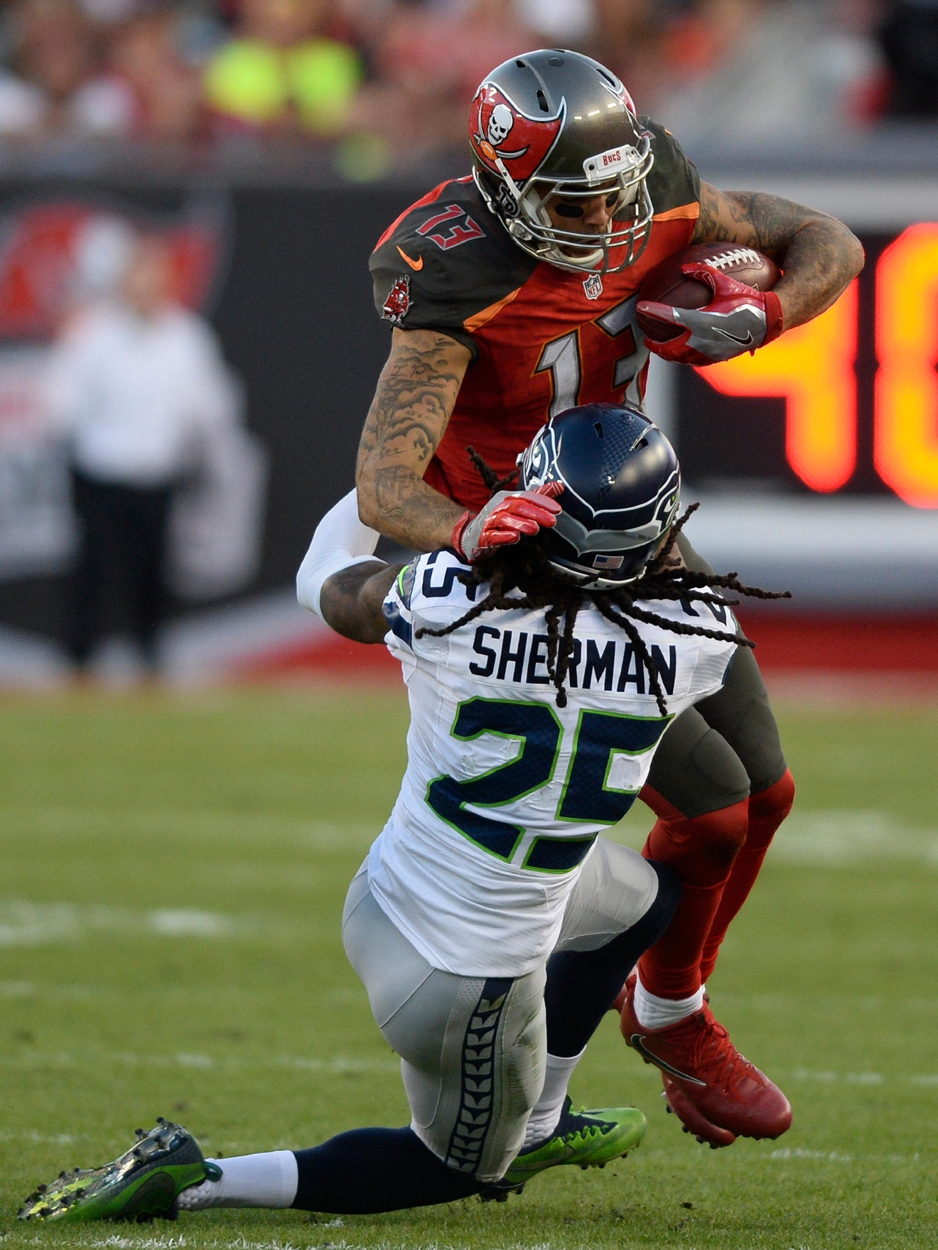 Seattle Seahawks cornerback Richard Sherman (25) stops Tampa Bay Buccaneers wide receiver Mike Evans (13) after a reception during the second quarter of an NFL football game Sunday, Nov. 27, 2016, in Tampa, Fla. (AP Photo/Jason Behnken)