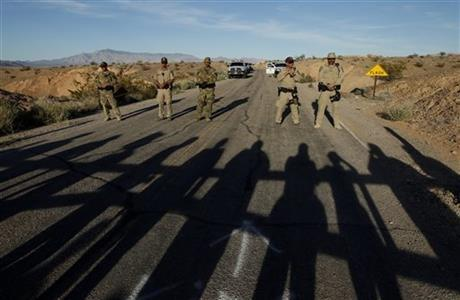 Federal law enforcement officers block a road at the Lake Mead National Recreation Area near Overton, Nev. Thursday, April 10, 2014.
