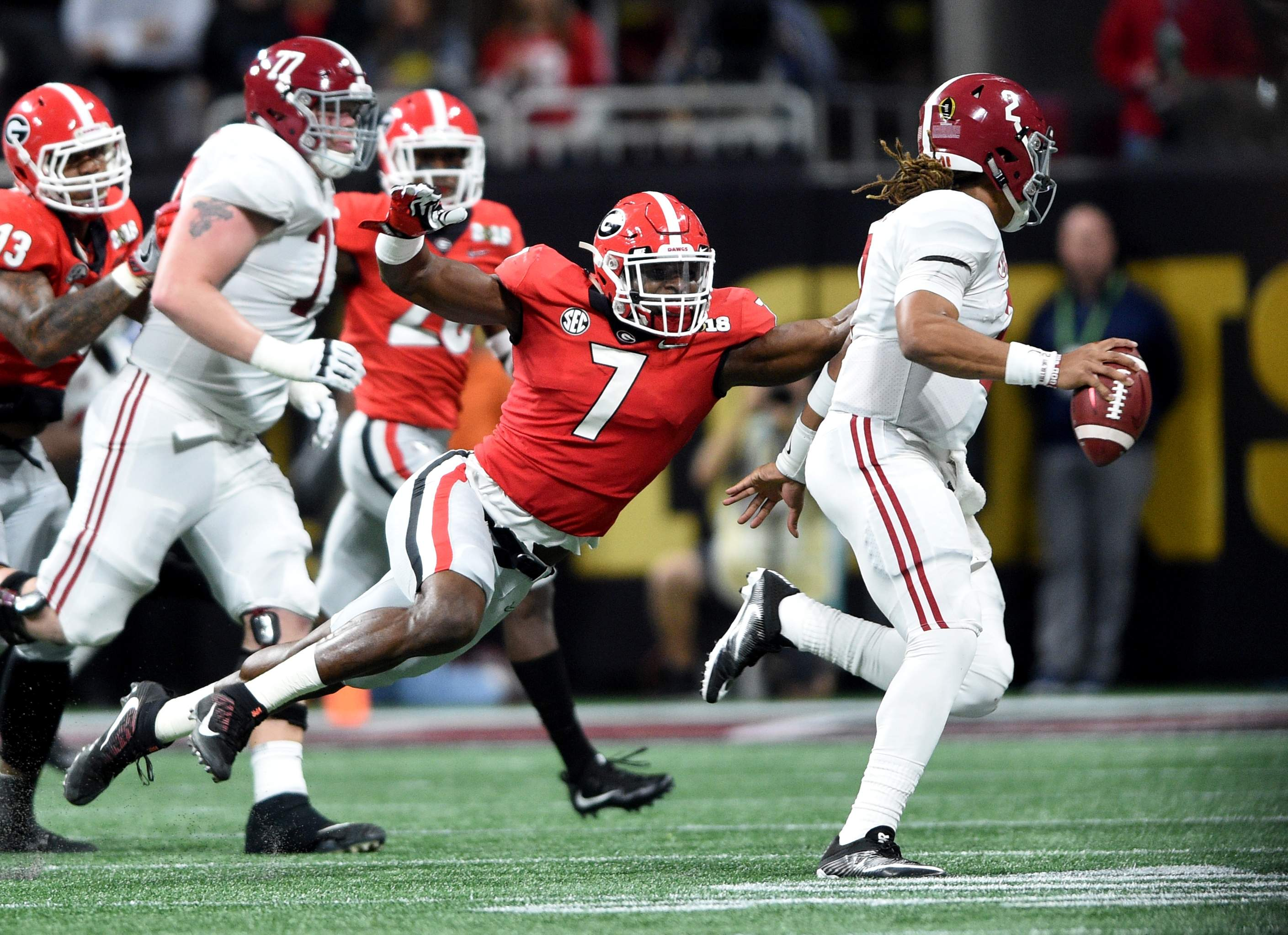 Georgia's Lorenzo Carter, left, stretches to get ahold of Alabama quarterback Jalen Hurts during the 2018 College Football Playoff National Championship at Mercedes-Benz Stadium in Atlanta, Ga., Monday evening January 8, 2018. MICHAEL HOLAHAN/AUGUSTA CHRONICLE