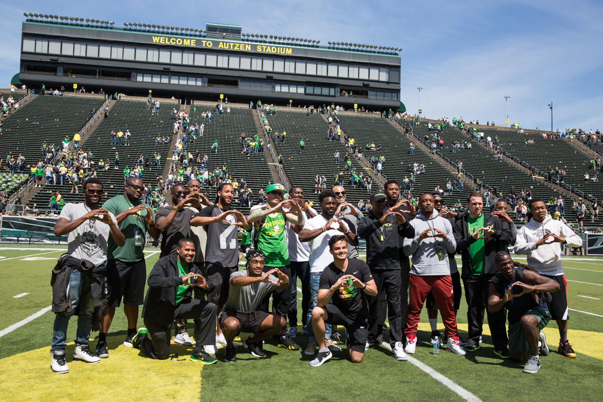 New Oregon Ducks Head Coach Willie Taggart throws his O with past members of the Oregon Ducks. The 2017 Oregon Ducks Spring Game provided fans their first look at the team under new Head Coach Willie Taggart's direction.  Team Free defeated Team Brave 34-11 on a sunny day at Autzen Stadium in Eugene, Oregon.  Photo by Austin Hicks, Oregon News Lab