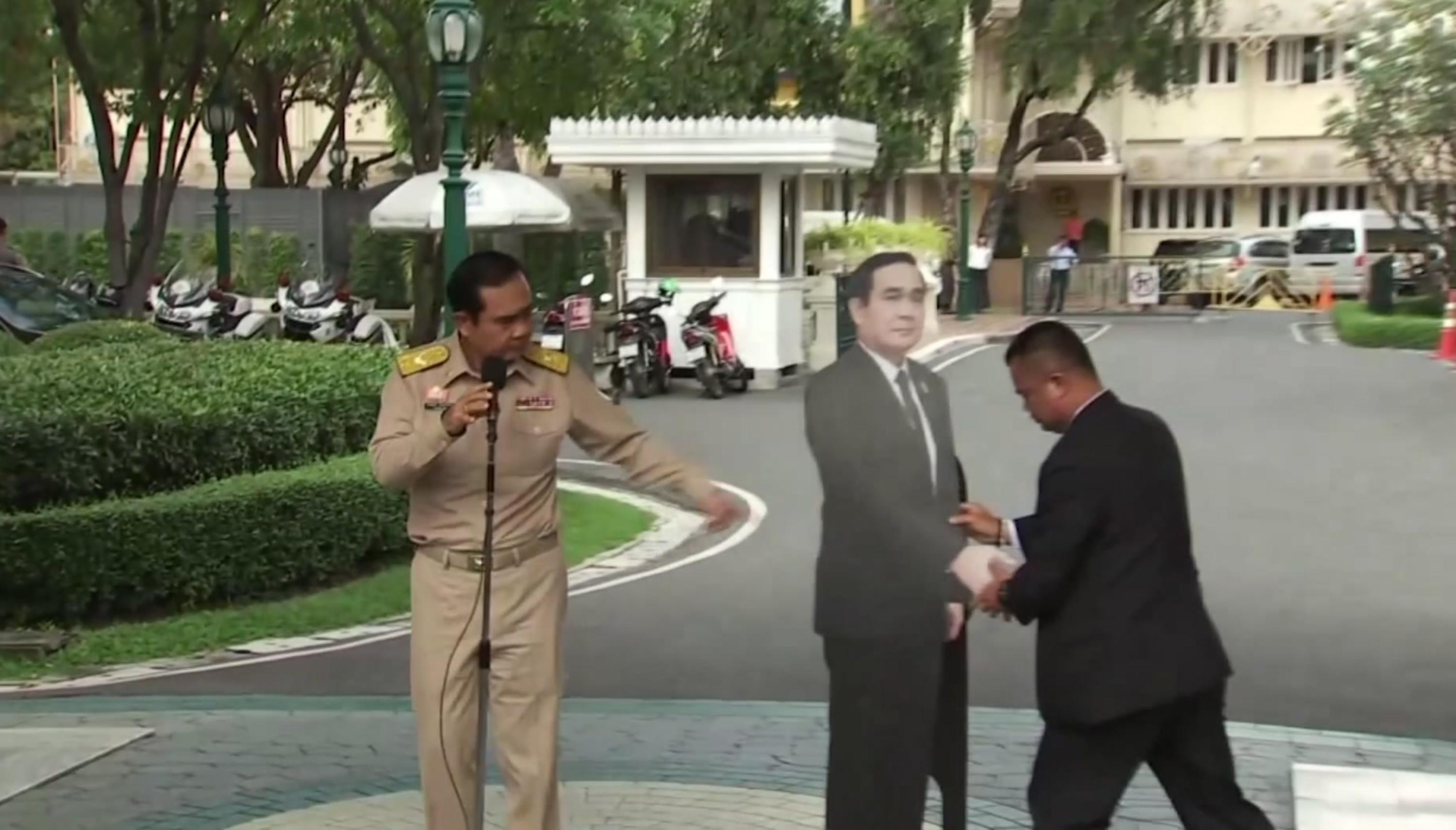 In this image from video, Thailand's Prime Minister Prayuth Chan-ocha, left, directs the scene as a life-sized cardboard cut-out figure of himself is carried into view by an aid, in Bangkok, Thailand, Monday Jan. 8, 2018. (TPBS via AP)<p></p>