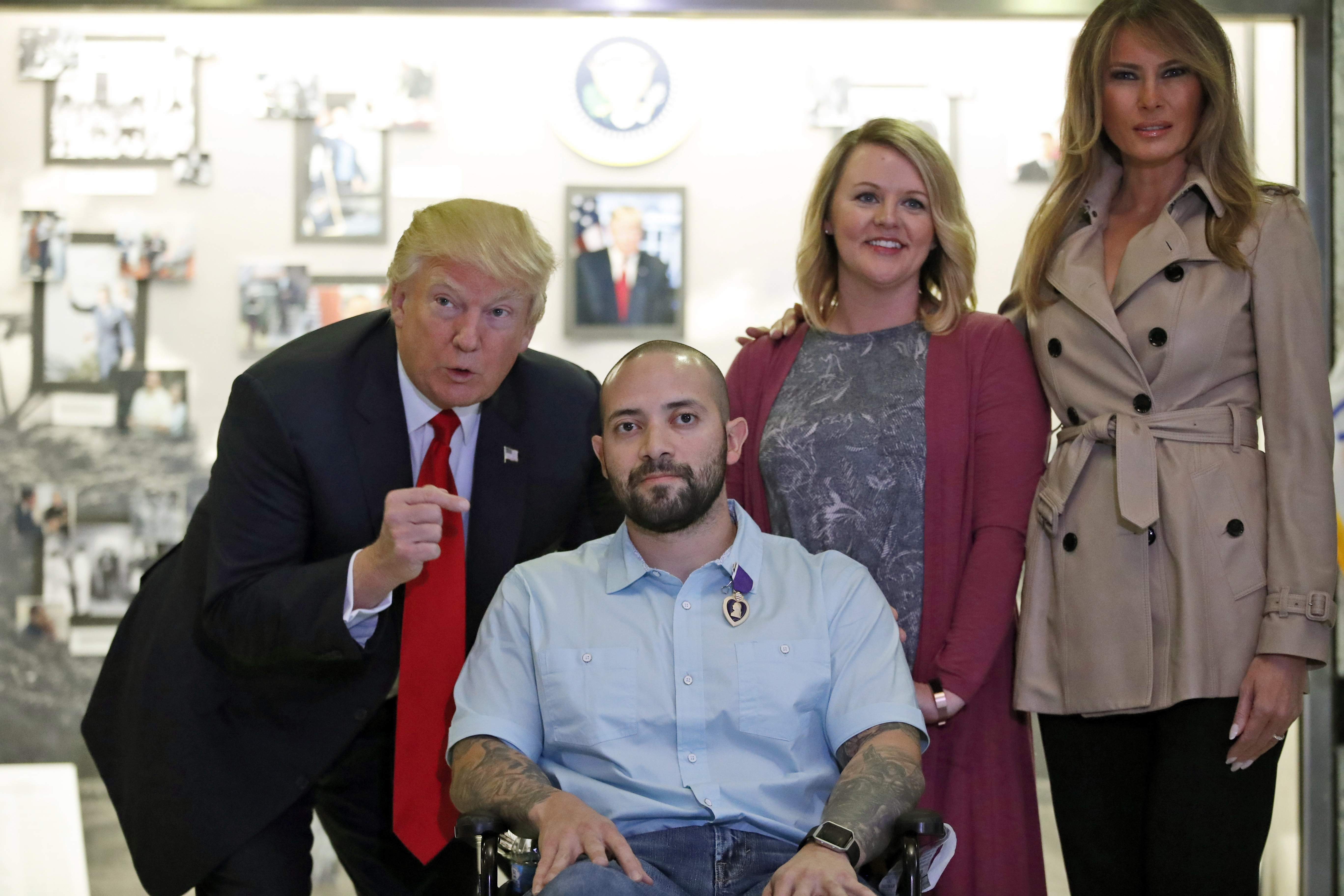 DAY 93 - In this April 22, 2017, file photo, President Donald Trump, left, points after awarding a Purple Heart to U.S. Army Sgt. 1st Class Alvaro Barrientos, with first lady Melania Trump, right, and Tammy Barrientos, second from right, at Walter Reed National Military Medical Center in Bethesda, Md. (AP Photo/Alex Brandon, File)