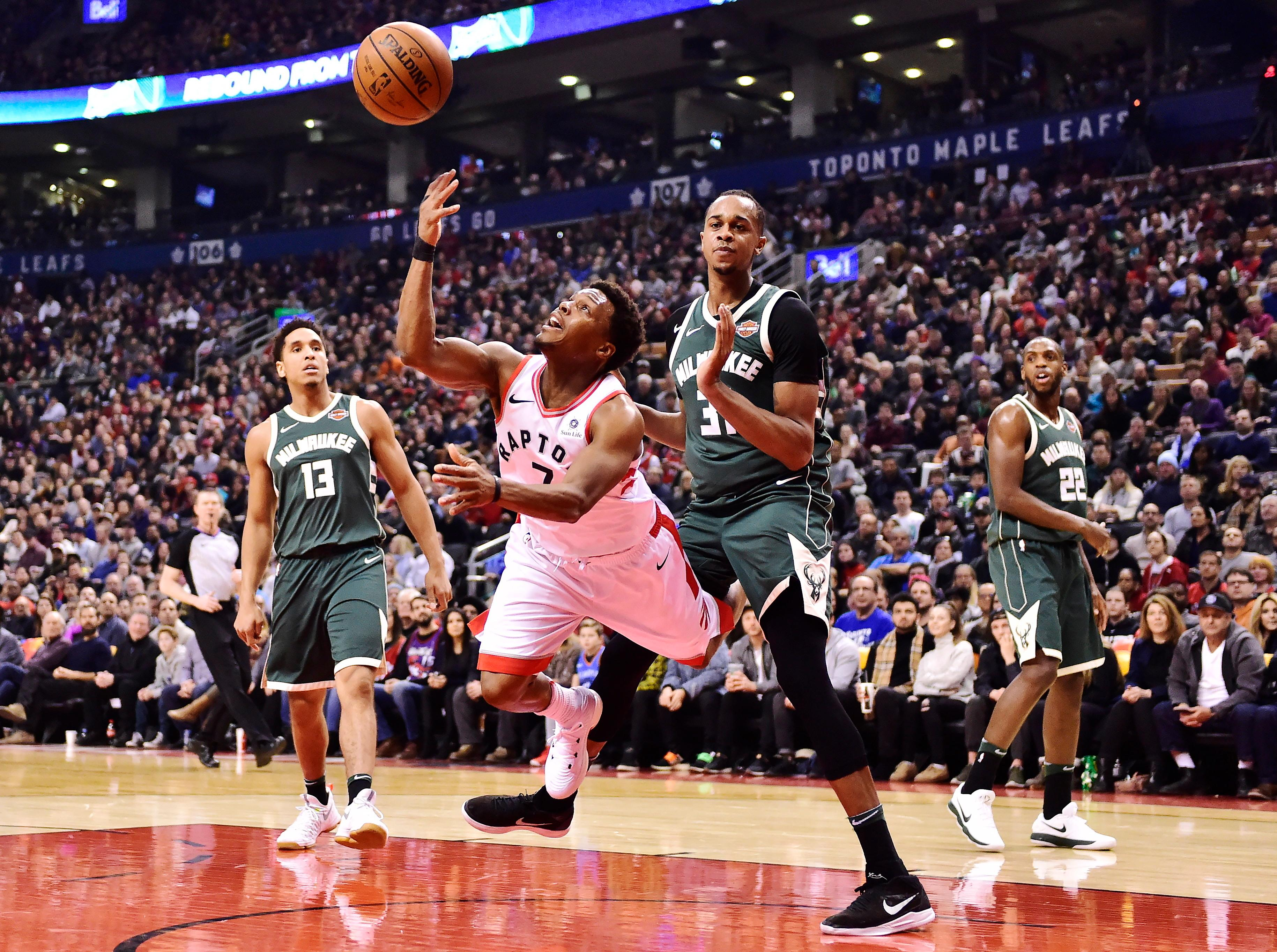 Toronto Raptors guard Kyle Lowry (7) throws up a shot as he is fouled by Milwaukee Bucks forward John Henson (31) during first half action in Toronto on Monday, Jan. 1, 2018. (Frank Gunn/The Canadian Press via AP)