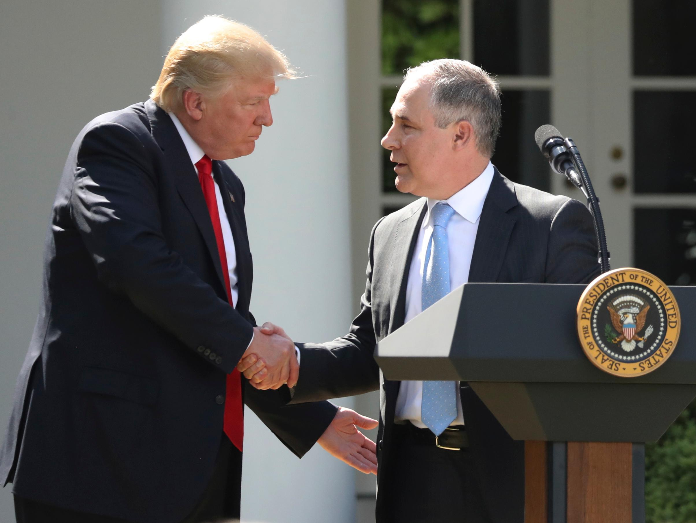 FILE - In this June 1, 2017 file photo, President Donald Trump shakes hands with EPA Administrator Scott Pruitt after speaking about the U.S. role in the Paris climate change accord in the Rose Garden of the White House in Washington. Trump and his cabinet often avoid talking about the science of climate change, but when pressed what they have said clashes with established mainstream science, data and peer-reviewed studies and reports. (AP Photo/Andrew Harnik, File)