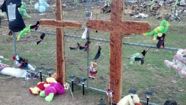 In front of the fence line, other crosses have appeared and hundreds of people are signing them.