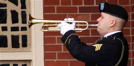 Sgt. Mark Koehl plays taps outside a memorial service Thursday, January 9, 2014, at Fort Riley, Kan. Soldiers and families paid their respects to five soldiers who were killed in a Black Hawk helicopter crash in December in Afghanistan.