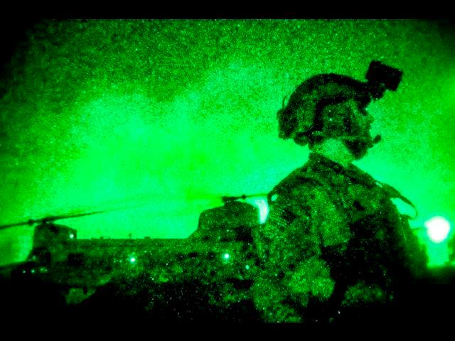 As seen through a night-vision device, a U.S. soldier watches as CH-47 Chinook helicopters touch down during an operation to disrupt insurgent movement in Afghanistan's Nangarhar province, March 21, 2014.
