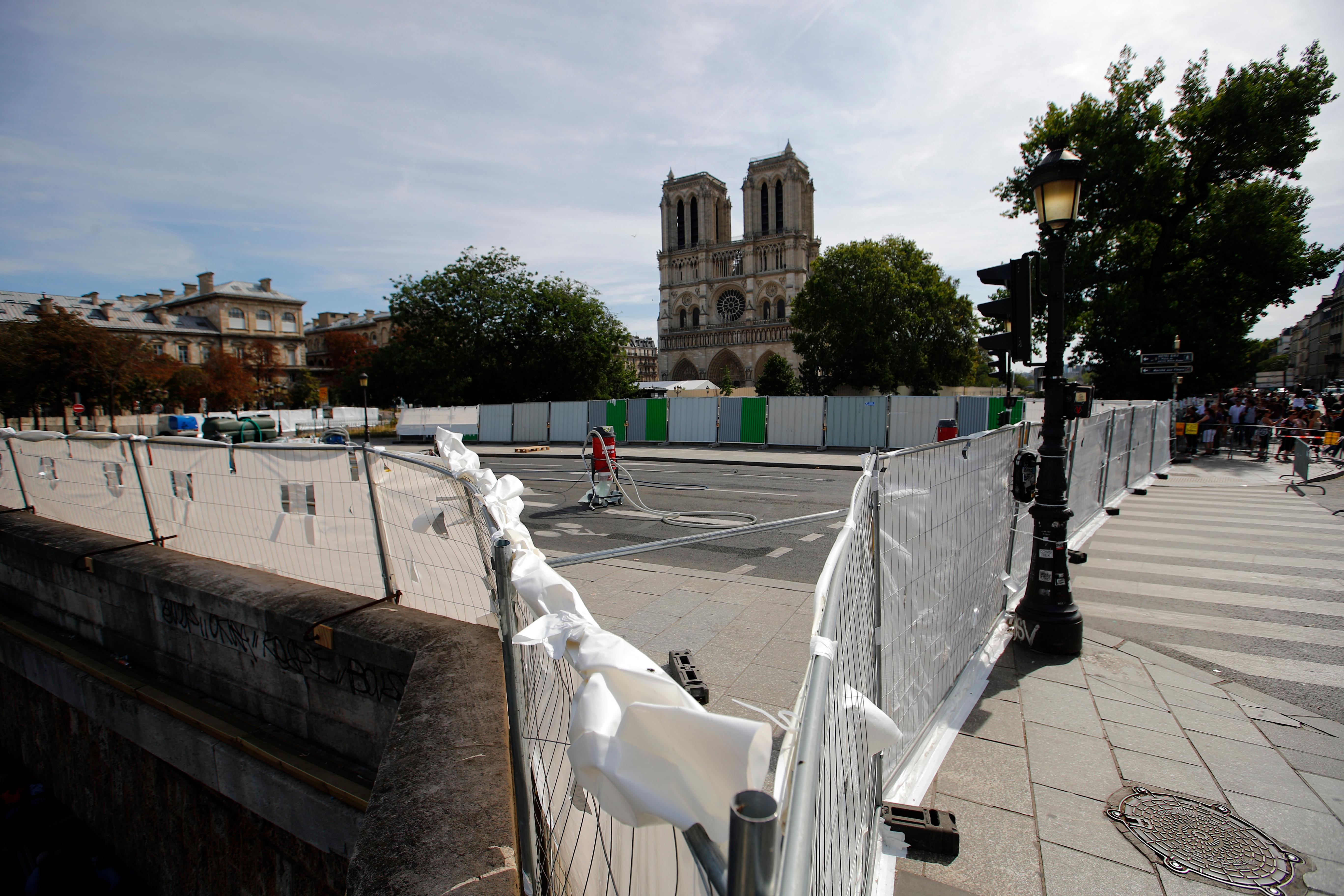 A vacuum cleaner stands amid protection panels securing a perimeter around the Notre Dame Cathedral ahead of the start of a massive lead decontamination in Paris, Friday, Aug. 16, 2019. (AP Photo/Francois Mori)