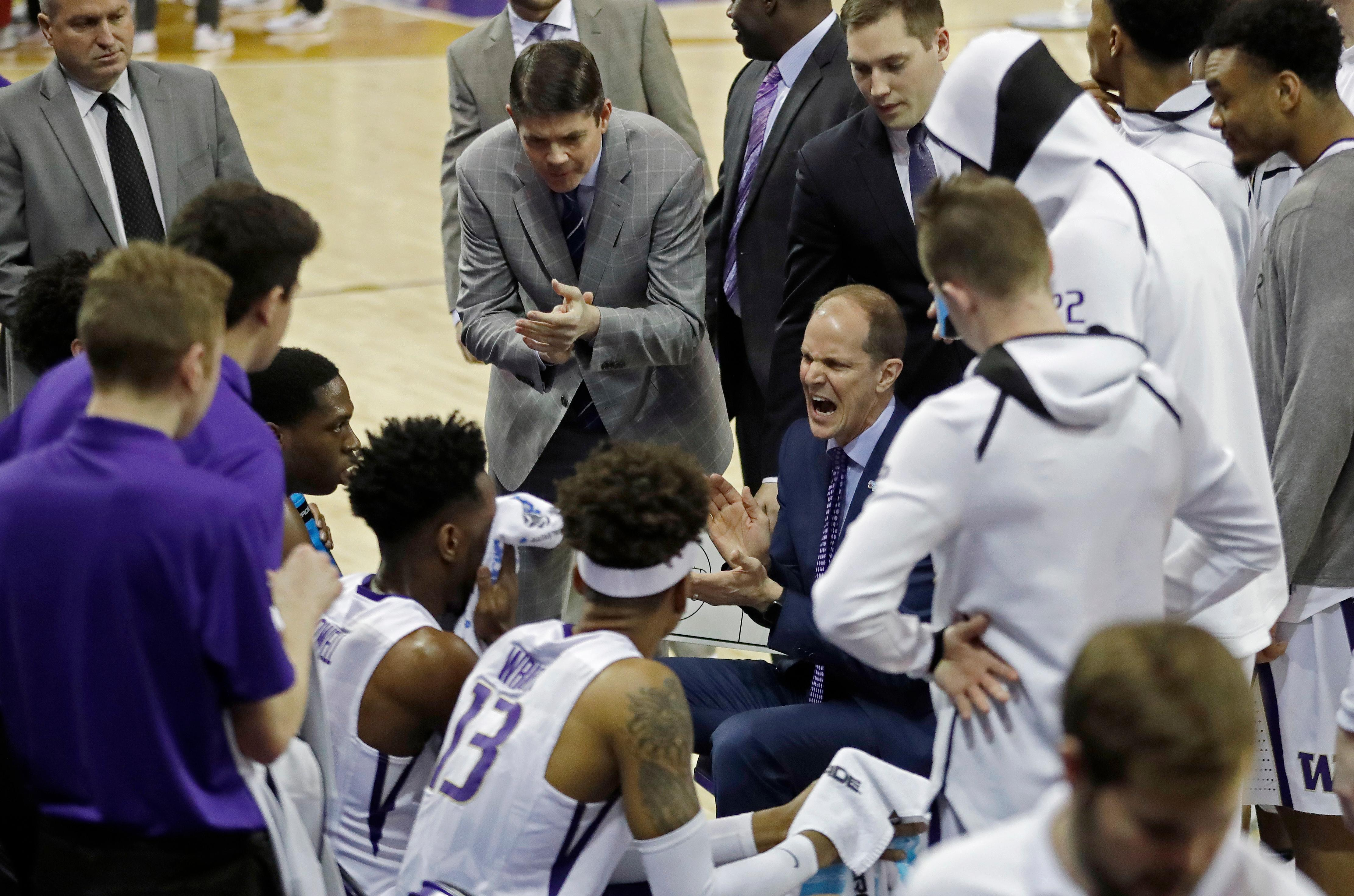 In this Sunday, Jan. 28, 2018 photo, Washington head coach Mike Hopkins, center right, fires up his team during a time out huddle at the bench during an NCAA college basketball game against Washington State in Seattle. One of the most surprising stories in college basketball is what Hopkins is doing in his first season at Washington and how the Huskies are in the conversation for an NCAA bid entering February. (AP Photo/Ted S. Warren)