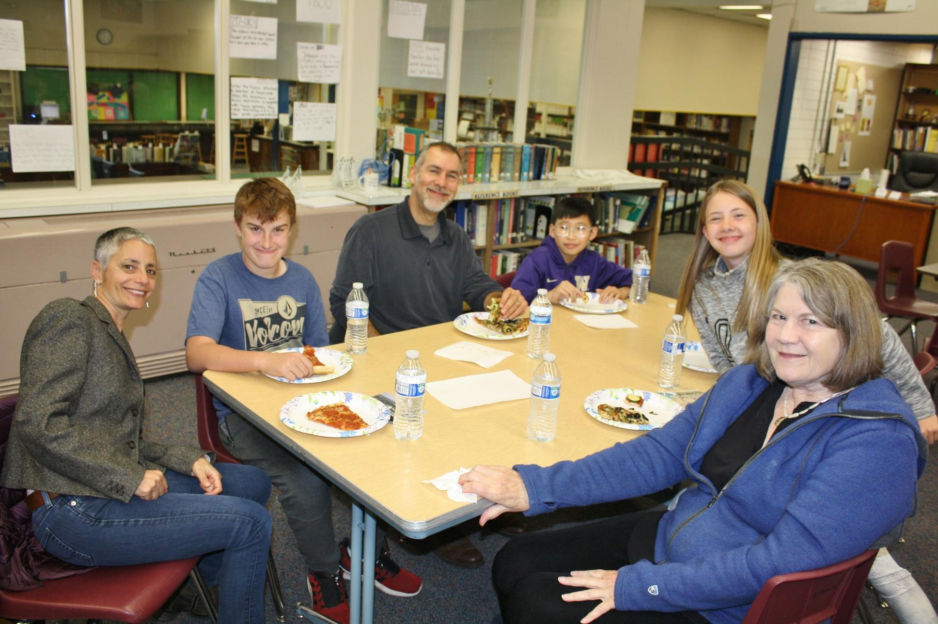 Courtesy photoMembers of the Ashland Kiwanis share pizza with their 'Postcard Buddies' at Ashland Middle School.