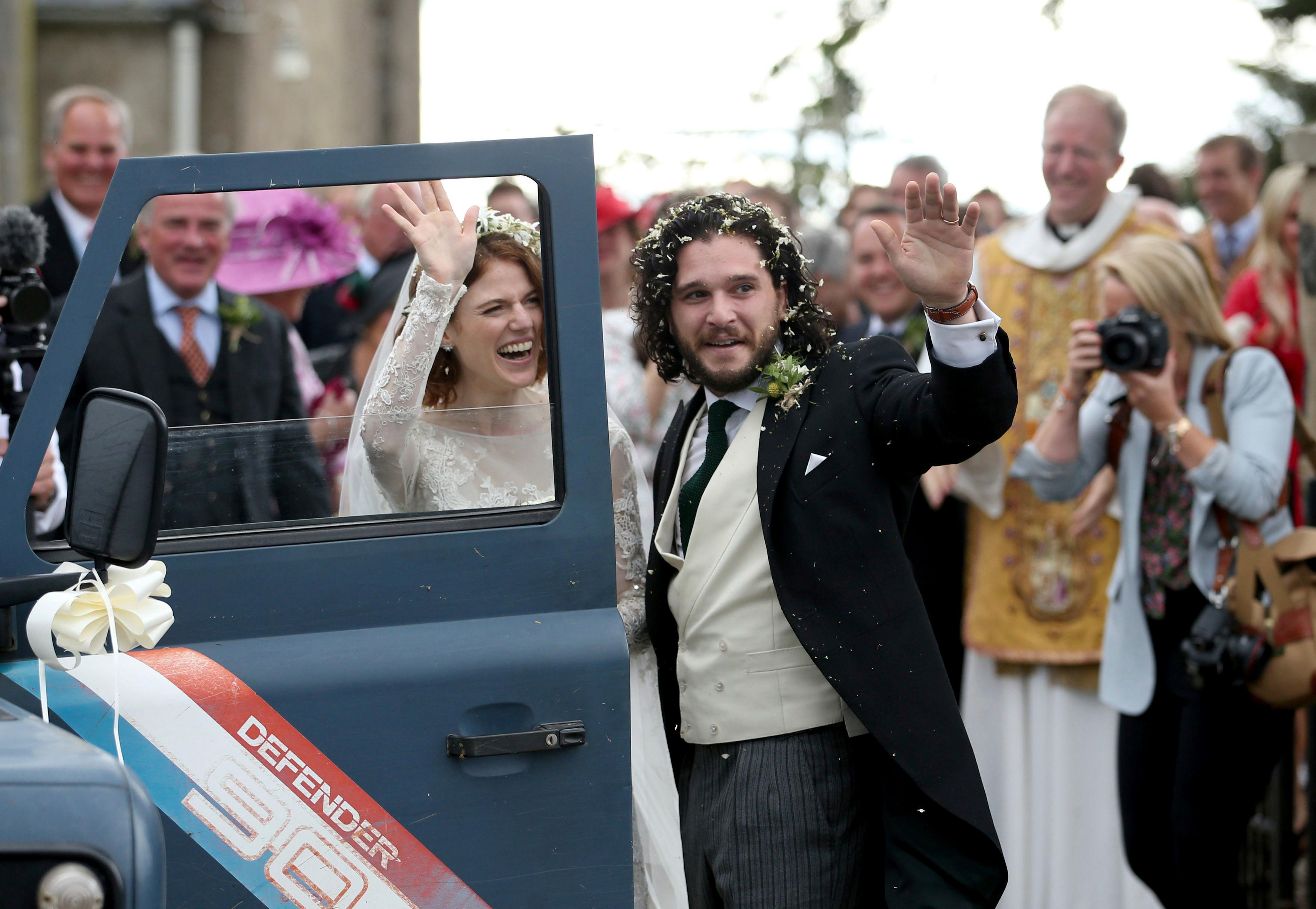 "Actors Kit Harington and Rose Leslie reacts as they leave after their wedding ceremony, at Rayne Church, Kirkton of Rayne in Aberdeenshire, Scotland, Saturday June 23, 2018. Former ""Game of Thrones"" co-stars Kiet Harington and Rose Leslie married near the bride's family castle in Scotland. The couple and guests arrived at Rayne Church, close to the 900-year-old Wardhill Castle in northeast Scotland, which is owned by Leslie's family. Harington, wearing a morning suit, and Leslie, in a flowing ivory gown, smiled at members of the public who had gathered outside the church. (Jane Barlow/PA via AP)"