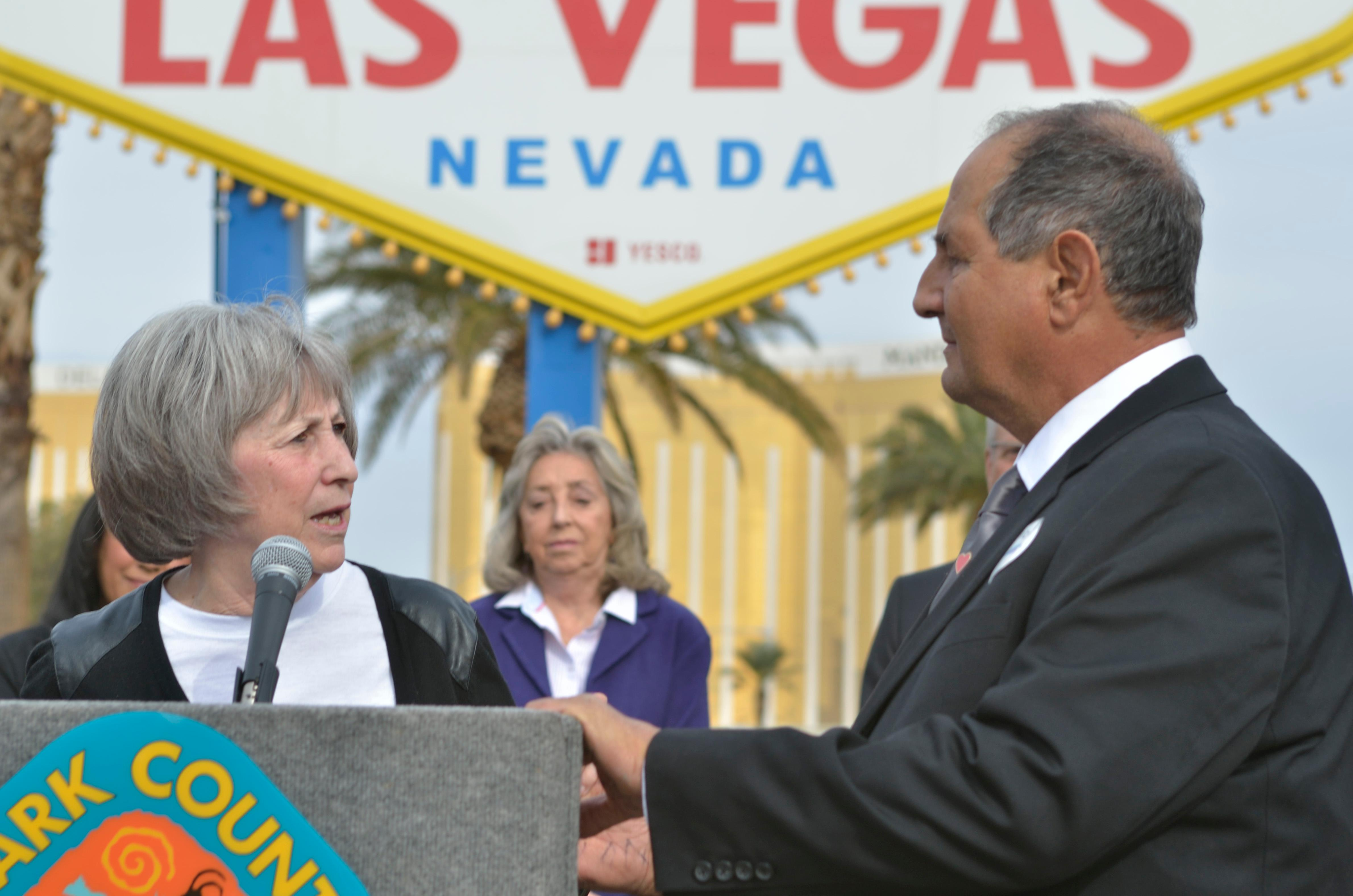 "Clark County Commissioner Susan Brager, left, speaks as Greg Zanis listens during ""Greg Zanis Day"" at the Welcome to Fabulous Las Vegas sign on the Las Vegas Strip on Sunday, Nov. 12, 2017. Zanis, a carpenter from Aurora, Ill., was recognized by the Clark County Commision for creating 58 crosses memorializing those who died during the Route 91 Harvest festival shooting on Oct. 1. The crosses were later moved to the Clark County Museum for its permanent collection. [Bill Hughes/Las Vegas News Bureau]"