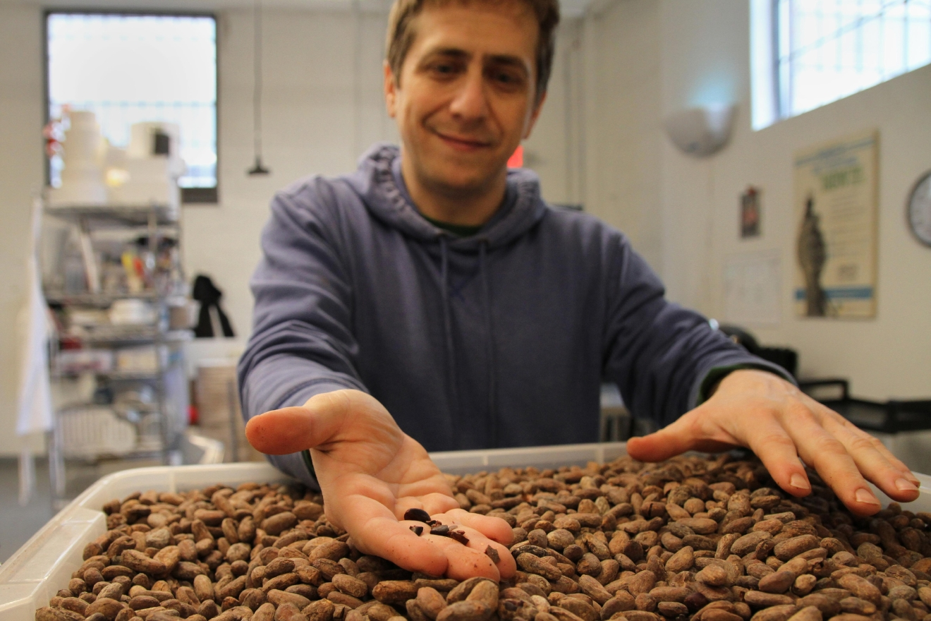 Undone Chocolate prepares the ingredients in shifts and Adam was unable to show the process called winnowing, where they separate the cacao bean's nibs from the shells. Adam is holding some of the nibs, which go into the chocolate. (Image: Amanda Andrade-Rhoades/ DC Refined)