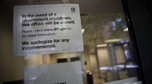 A sign is posted in the window of an IRS office in Brooklyn notifying that the office is closed due to the government shutdown on October 1.