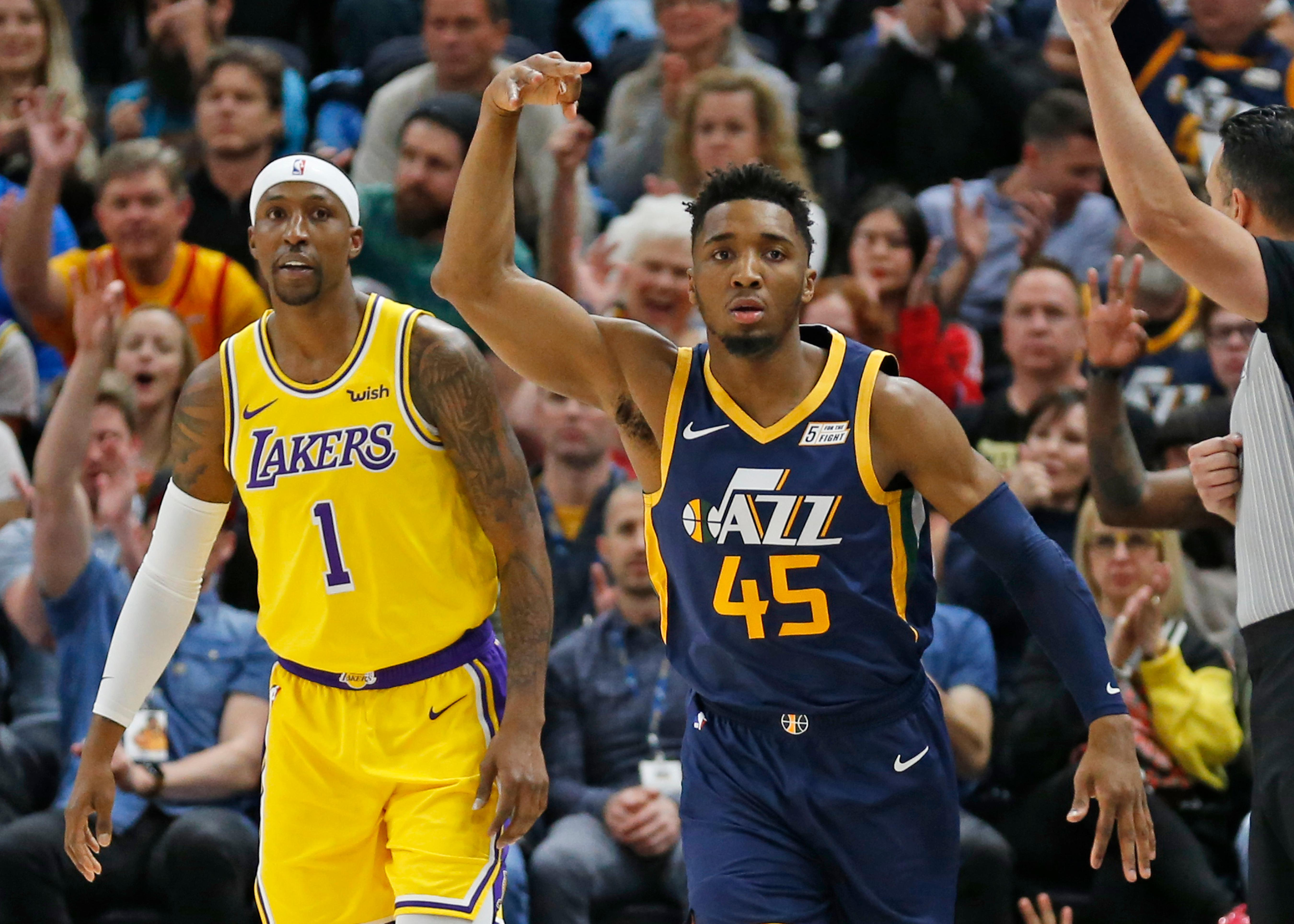 Utah Jazz guard Donovan Mitchell (45) celebrates after scoring 3-pointer against Los Angeles Lakers guard Kentavious Caldwell-Pope (1) during the first half of an NBA basketball game Wednesday, March 27, 2019, in Salt Lake City. (AP Photo/Rick Bowmer)