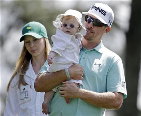 Hunter Mahan carries his daughter Zoe as he walks down the first fairway with his wife Kandi during the par three competition at the Masters golf tournament Wednesday, April 9, 2014, in Augusta, Ga.