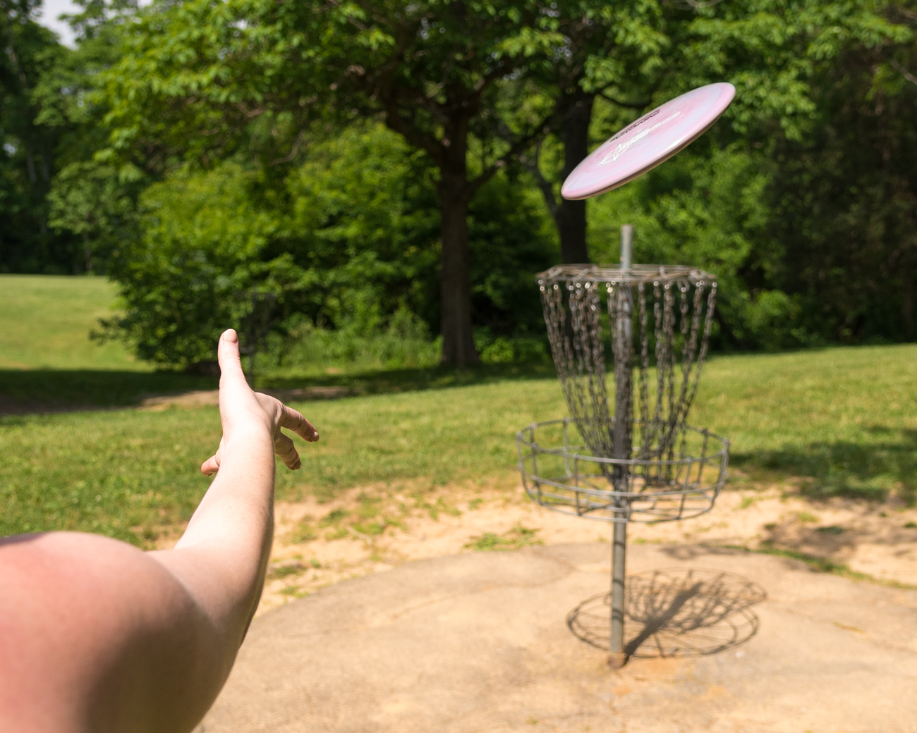 "The object of disc golf is simple: stand on a concrete platform and take as few throws of the disc as possible to land in the metal basket at the end of the ""hole."" The rules are similar(ish) to traditional golf, albeit with a frisbee component instead of a golf ball and club. / Image: Phil Armstrong, Cincinnati Refined // Published: 6.8.17"