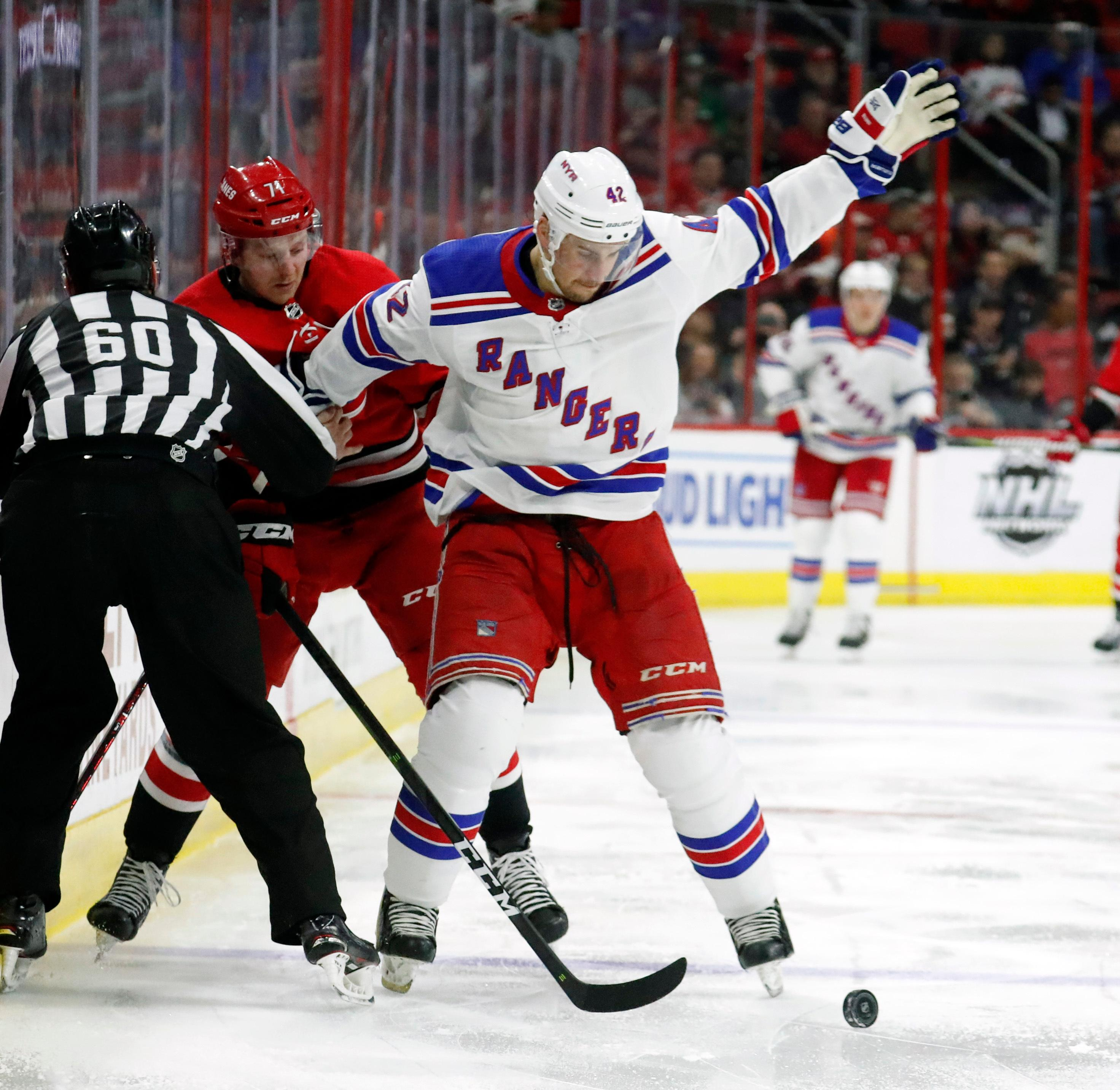 Carolina Hurricanes' Lucas Wallmark (71) of Sweden battles New York Rangers' Brendan Smith (42) during the second period of an NHL hockey game in Raleigh, N.C., Tuesday, Feb. 19, 2019. (AP Photo/Chris Seward)