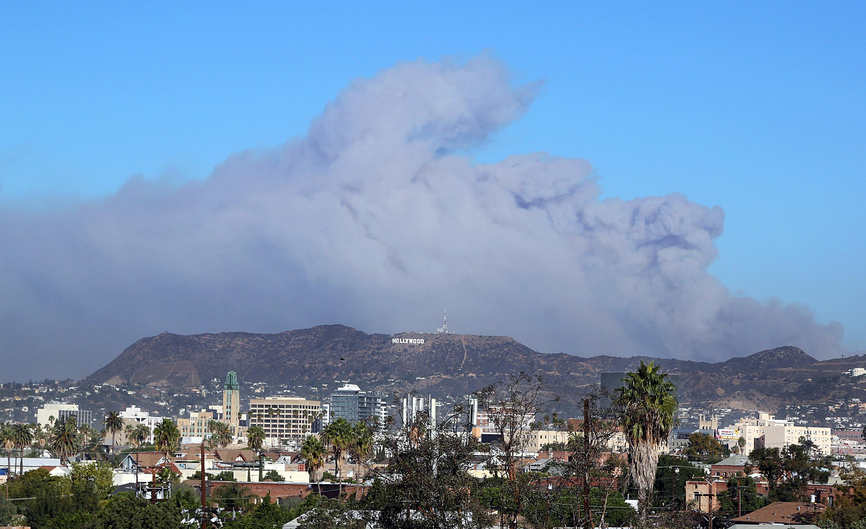 Smoke from the Creek wildfire in the San Gabriel Mountains, the second range behind the Hollywood Hills, home of the Hollywood sign, looms up over Los Angeles Tuesday morning, Dec. 5, 2017 (AP Photo/Reed Saxon)
