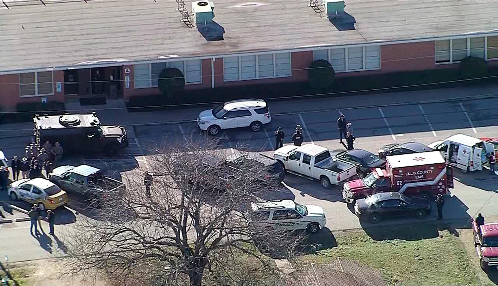 In this photo from video by KDFW Fox4, law enforcement personnel gather outside the high school in Italy, Texas, following an active shooter incident at the school Monday morning, Jan. 22, 2018. Sheriff's officials said a boy who is a student at the school was taken into custody. (KDFW Fox4 via AP)