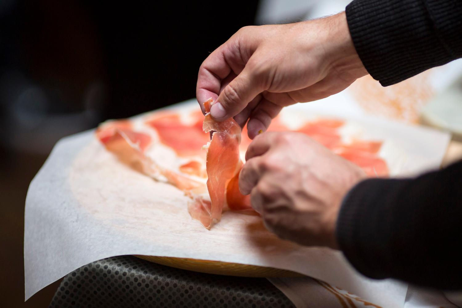 Pietro Borghesi, co-founder of La Spiga, cuts into the Proscuitto di Parma. This pig thigh had been hanging for two and half years. Each piece is hand cut, so it is a tedious process but would lose flavor if cut through a meat slicer. (Image: Sy Bean / Seattle Refined).