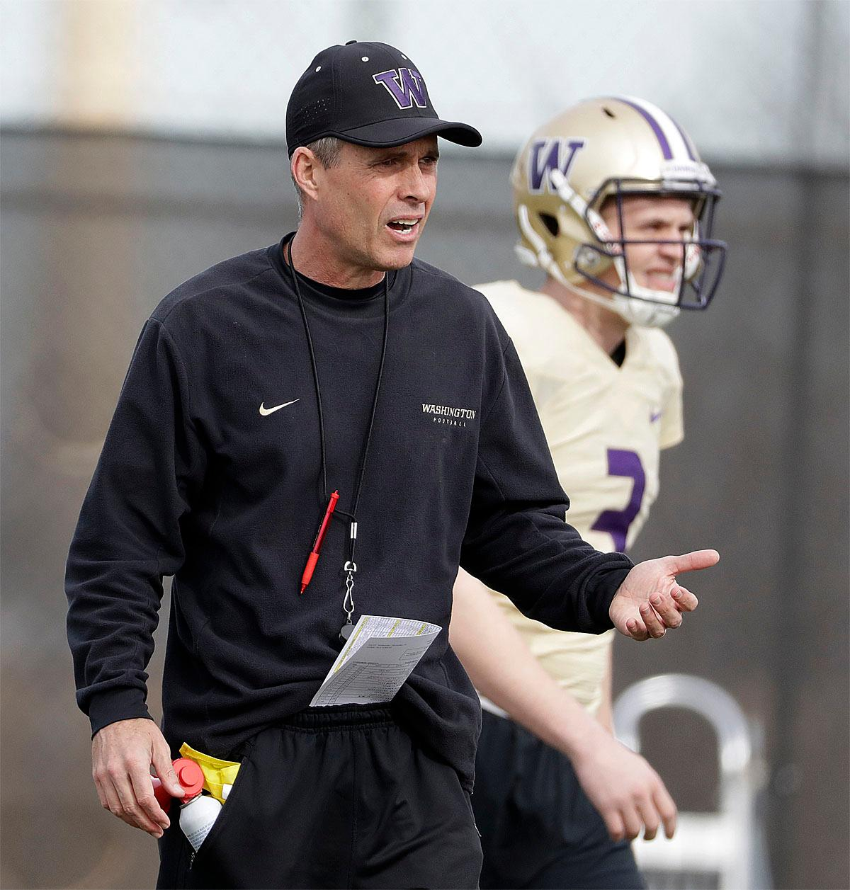 Washington head coach Chris Petersen, left, walks on the field next to quarterback Jake Browning during a Peach Bowl NCAA college football practice in Atlanta, Wednesday, Dec. 28, 2016. Alabama and Washington will face off in the Peach Bowl football game Saturday. (AP Photo/David Goldman)