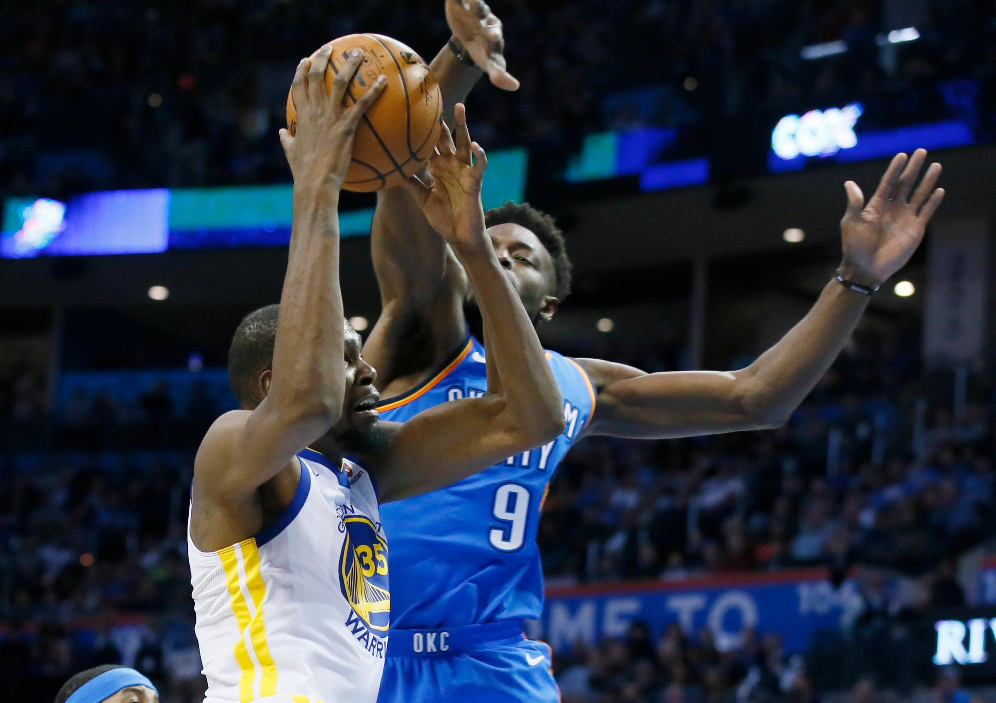 Golden State Warriors forward Kevin Durant, left, has a shot blocked by Oklahoma City Thunder forward Jerami Grant (9) during the first quarter of an NBA basketball game in Oklahoma City, Wednesday, Nov. 22, 2017. (AP Photo/Sue Ogrocki)