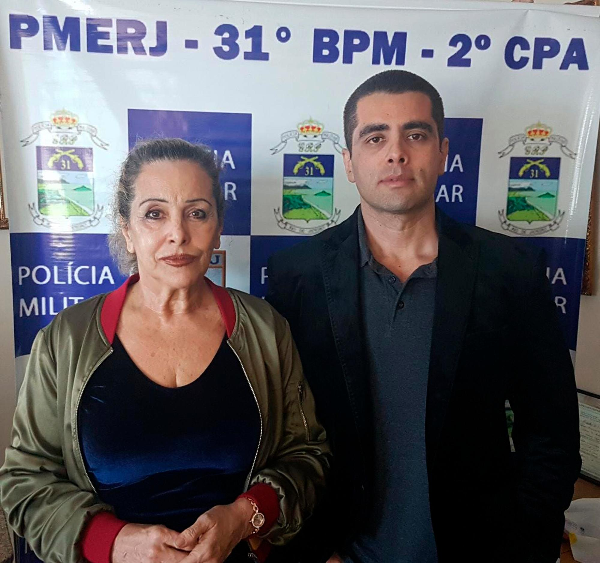 "This photo released by the Rio de Janeiro Military Police press office shows Dr. Denis Cesar Barros Furtado, right, and his mother Maria de Fatima Barros, who were arrested in Rio de Janeiro, Brazil, Thursday, July 19, 2018. The 45-year-old buttocks enlargement specialist, also known as Dr. ""Bumbum"" or Dr. Fanny, fled when one of his female patients died after a surgical procedure conducted in his apartment. (AP Photo/Military Police Press Office)"