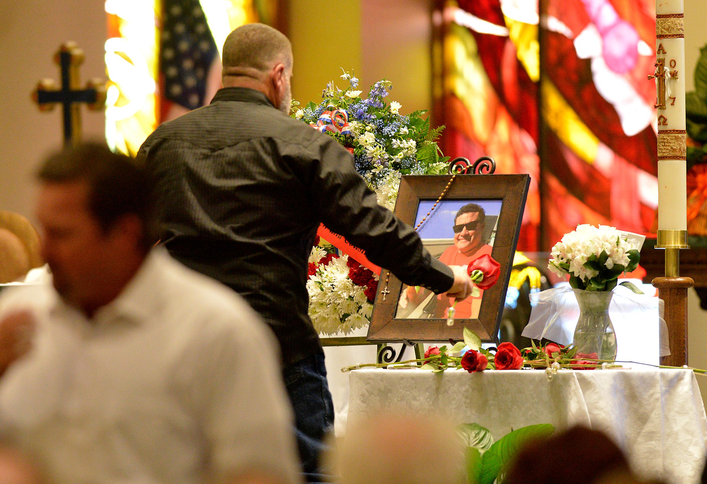 A pallbearer lays a rose next to a photo of Jack Beaton during his memorial service at St. Elizabeth Ann Seton Catholic Church in Bakersfield, Calif., on Saturday, Oct. 7, 2017. Beaton was a victim of the Oct. 1 mass shooting in Las Vegas. (AP Photo/Silvia Flores)
