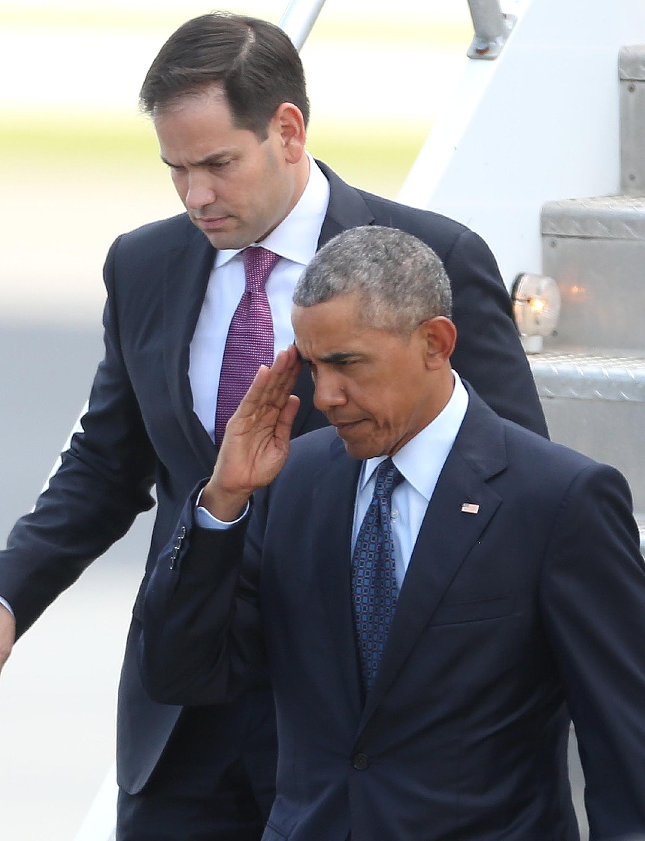 President Obama salutes in front of Florida Sen. Marco Rubio, top, after as the president deplanes after his arrival at Orlando International Airport, Thursday, June 16, 2016, in Orlando, Fla. Obama is in Orlando today to pay respects to the victims of the Pulse nightclub shooting and meet with families of victims of the attack. (Stephen M. Dowell/Orlando Sentinel via AP) MAGS OUT; NO SALES; MANDATORY CREDIT