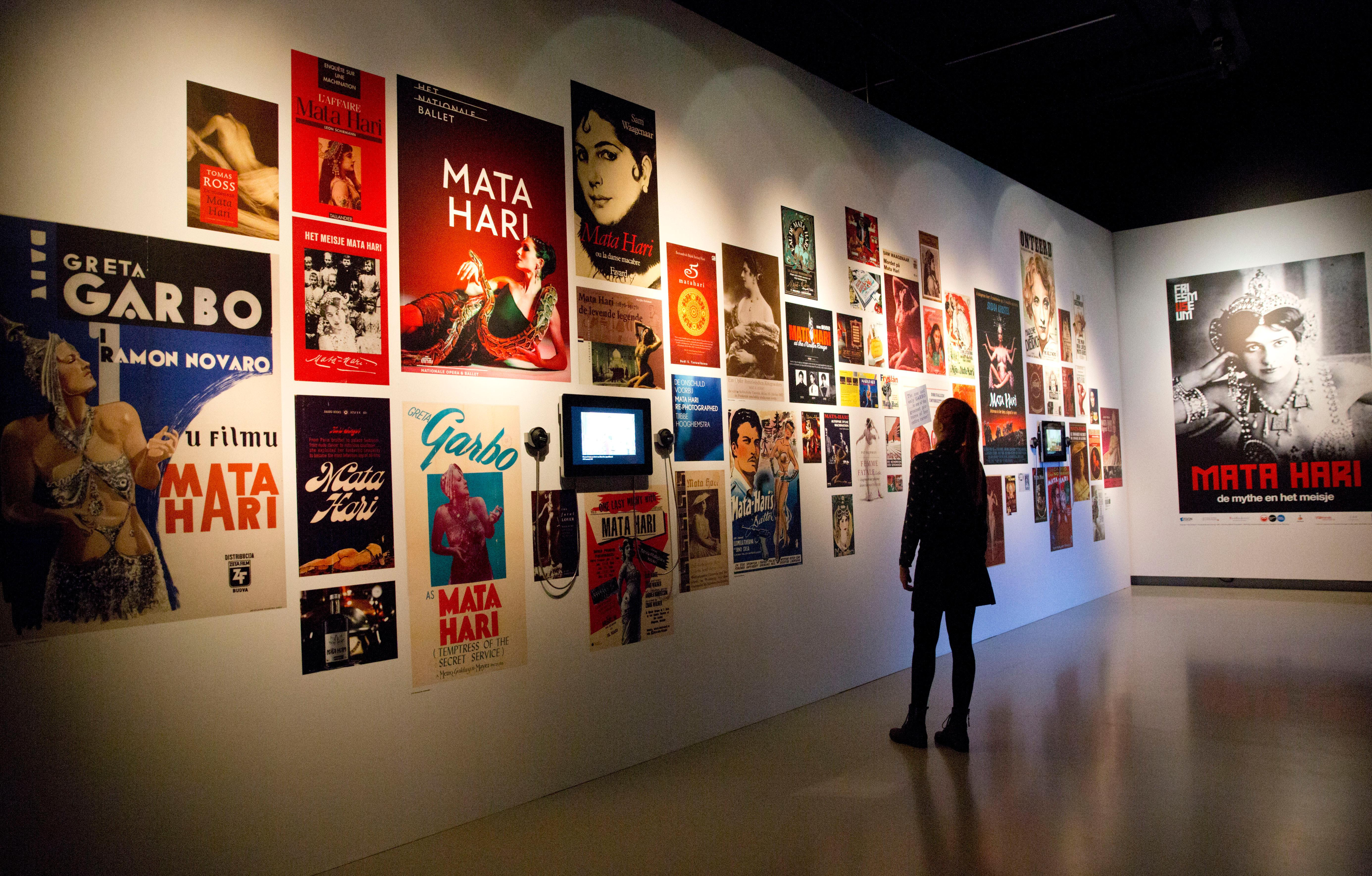 In this photo taken on Friday, Oct. 13, 2017, a visitor views posters of movies that have been made about Margaretha Zelle, also known as Mata Hari, at the Fries Museum in Leeuwarden, Netherlands. A century ago, on Oct. 15, 1917, an exotic dancer named Mata Hari was executed by a French firing squad, condemned as a sultry Dutch double agent who supposedly led tens of thousands of soldiers to their death during World War I. (AP Photo/Virginia Mayo)