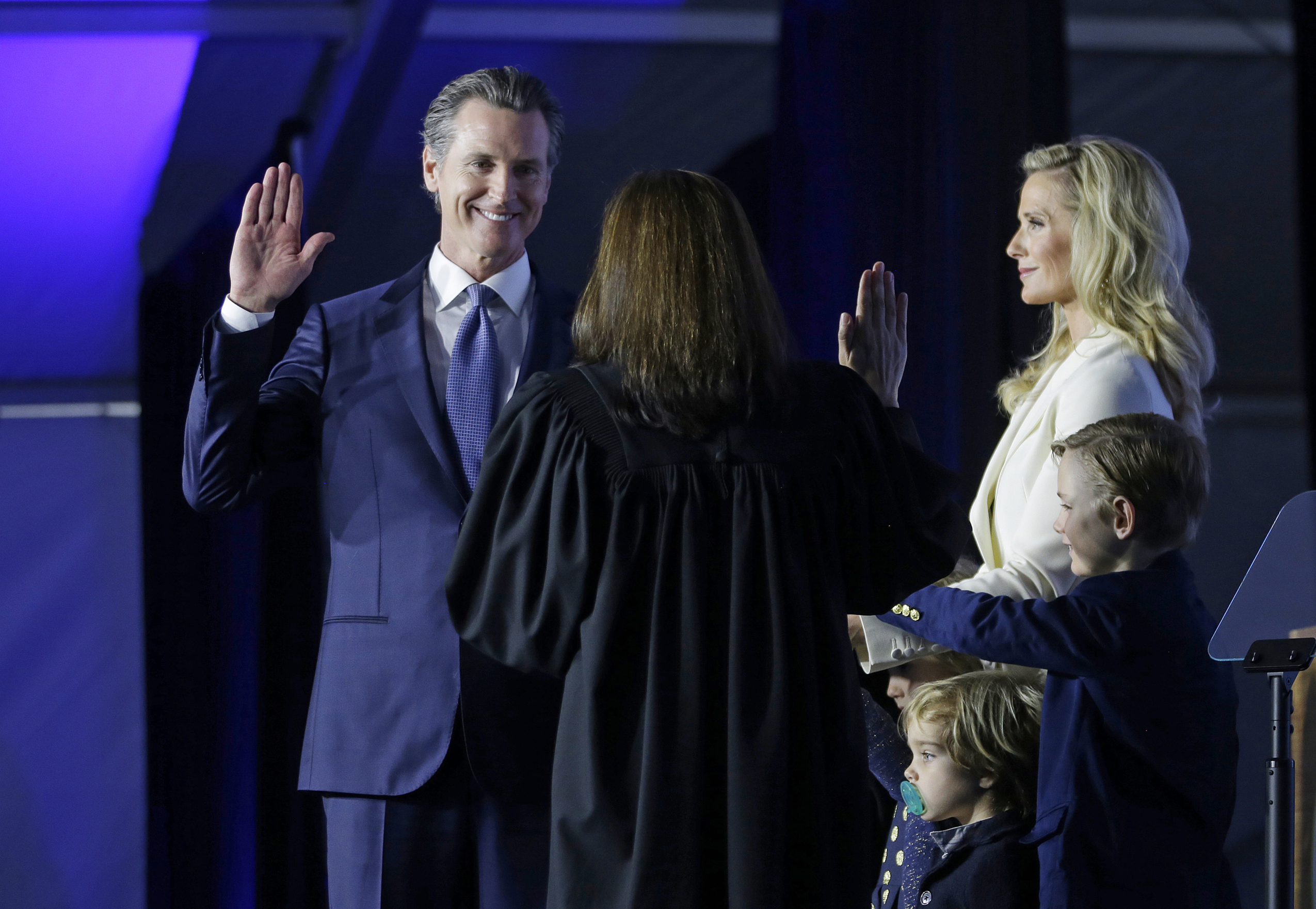 FILE - In this Jan. 7, 2019, file photo, California Governor Gavin Newsom takes the oath of office from state Supreme Court Chief Justice Tani Gorre Cantil-Sakauye during his inauguration in Sacramento, Calif. Looking on is Newsom's wife, Jennifer Siebel Newsom and their sons, Dutch, second from right, and Hunter, right. Newly elected California Gov. Gavin Newsom announced plans to expand Medicaid to those in the country illegally up to age 26 and implement a mandate that everyone buy insurance or face a fine. (AP Photo/Rich Pedroncelli, File)
