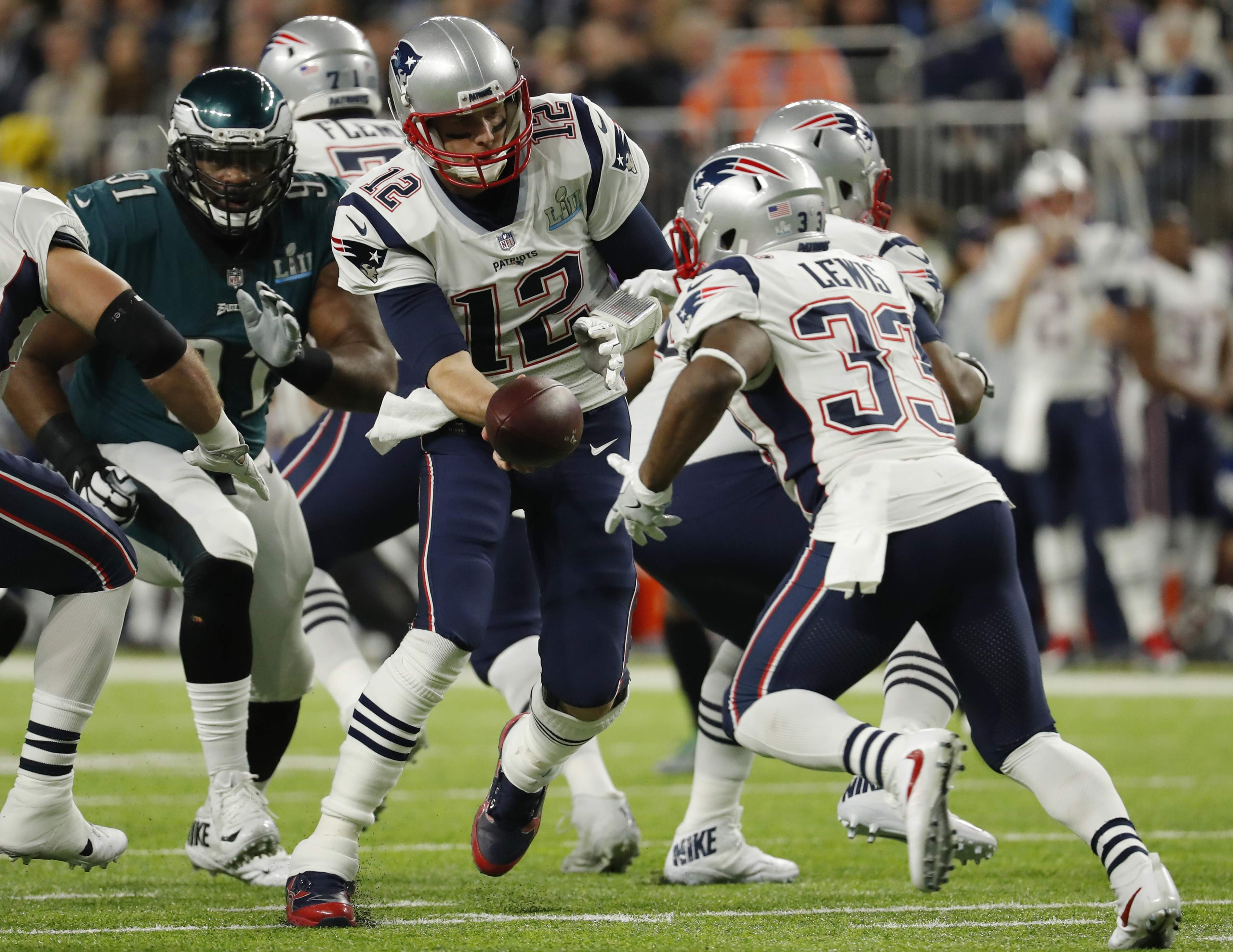 New England Patriots quarterback Tom Brady (12) hands the ball to running back Dion Lewis (33), during the first half of the NFL Super Bowl 52 football game against the Philadelphia Eagles, Sunday, Feb. 4, 2018, in Minneapolis. (AP Photo/Charlie Neibergall)