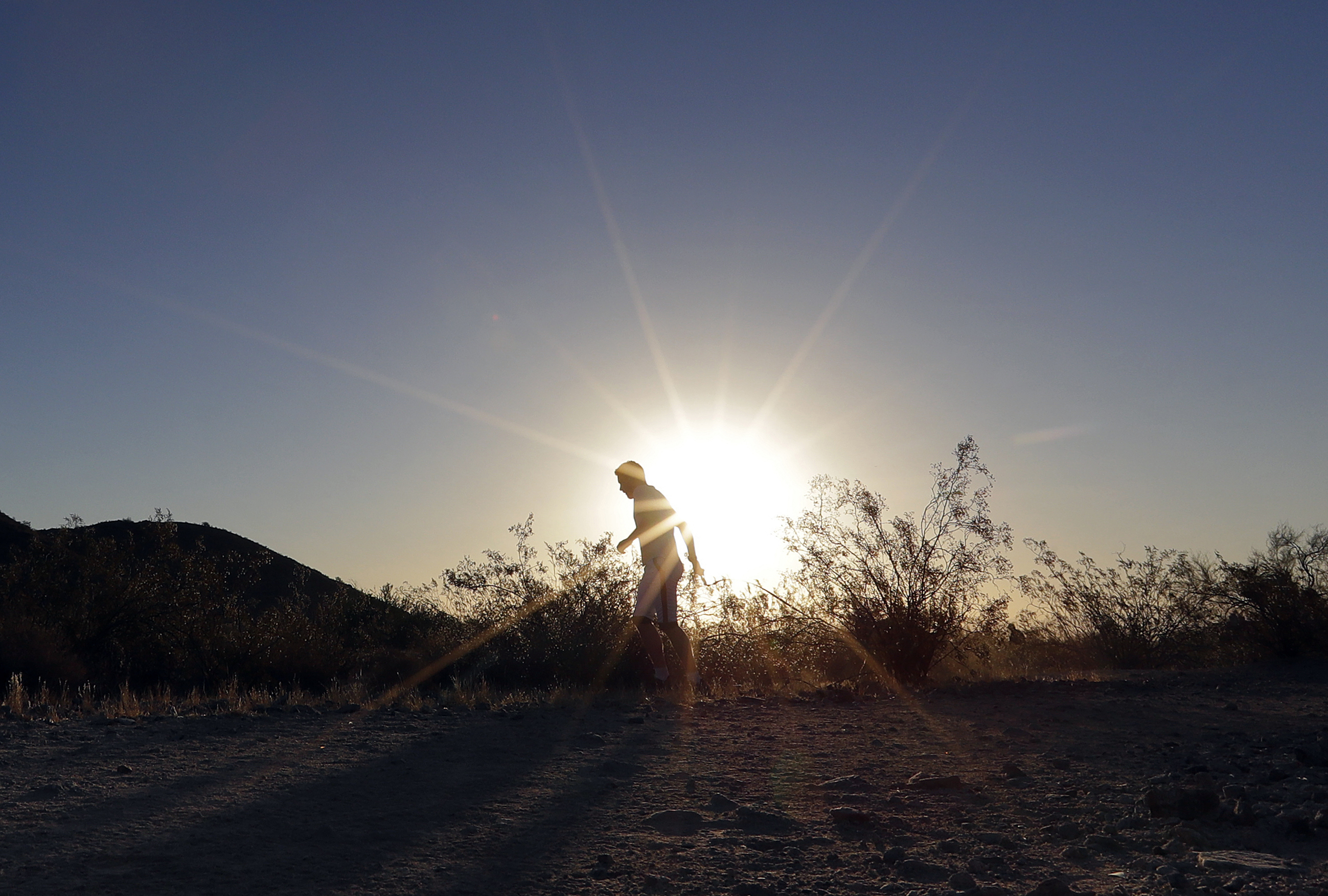 FILE - In this June 16, 2017, file photo, a man runs through section of South Mountain Park at sunrise to avoid the excessive heat in Phoenix. A record heat wave is rolling into Arizona, Nevada and California, threatening to bring 120-degree temperatures to Phoenix by early next week. The southwestern U.S. is about to feel the wrath of a punishing heat wave that includes a forecast of 120 degrees in Phoenix _ a temperature not seen in the desert city in more than 20 years. (AP Photo/Matt York, File)