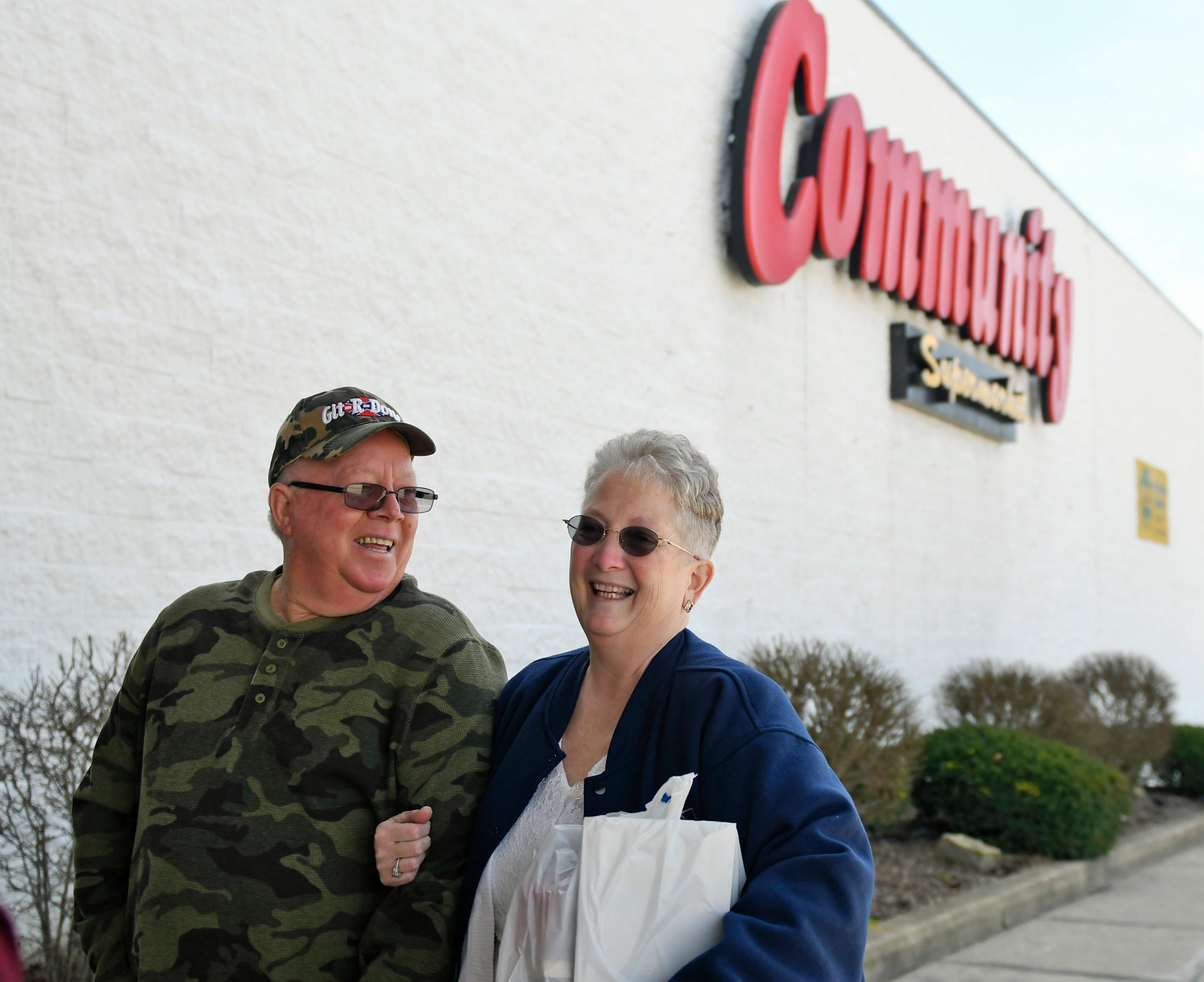 In this April 1, 2018 photo, Larry Spiering and Becky Smith pose for a photo outside where they held their wedding ceremony at the Community Market in Lower Burrell, Pa. Smith said she was working at the supermarket when Spiering walked up and gave her a piece of paper with his name and phone number on it. She said it was only fitting that they married in the aisle where they met. (Jack Fordyce/Pittsburgh Tribune-Review via AP)