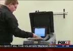 Brown County Deputy Clerk Justin Schmit feeds a ballot into the new voting machine.