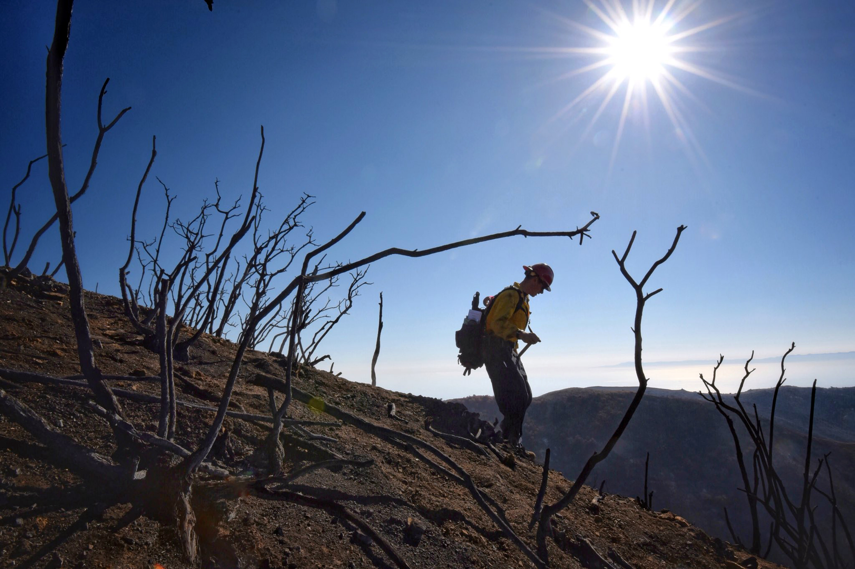 In this photo provided by the Santa Barbara County Fire Department, Santa Barbara County Fire Capt. Ryan Thomas hikes down steep terrain below East Camino Cielo to meet with his crew and root out and extinguish smoldering hot spots in Santa Barbara, Calif., Tuesday, Dec. 19, 2017. Officials estimate that the Thomas Fire will grow to become the biggest in California history before full containment, expected by Jan. 7, 2018. (Mike Eliason/Santa Barbara County Fire Department via AP)