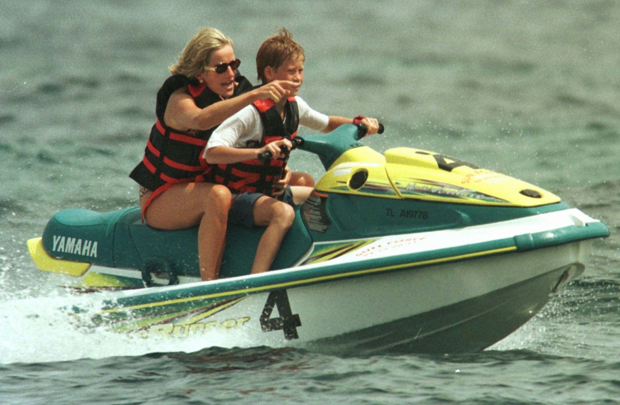 "FILE - In this Thursday July 17, 1997 file photo, Britain's Princess Diana rides a personal watercraft with her son Prince Harry, steering, in Saint Tropez, on the French Riviera, where she is spending a few days holidaying. It has been 20 years since the death of Princess Diana in a car crash in Paris and the outpouring of grief that followed the death of the ""people's princess."" (AP Photo/Lionel Cironneau, File)"